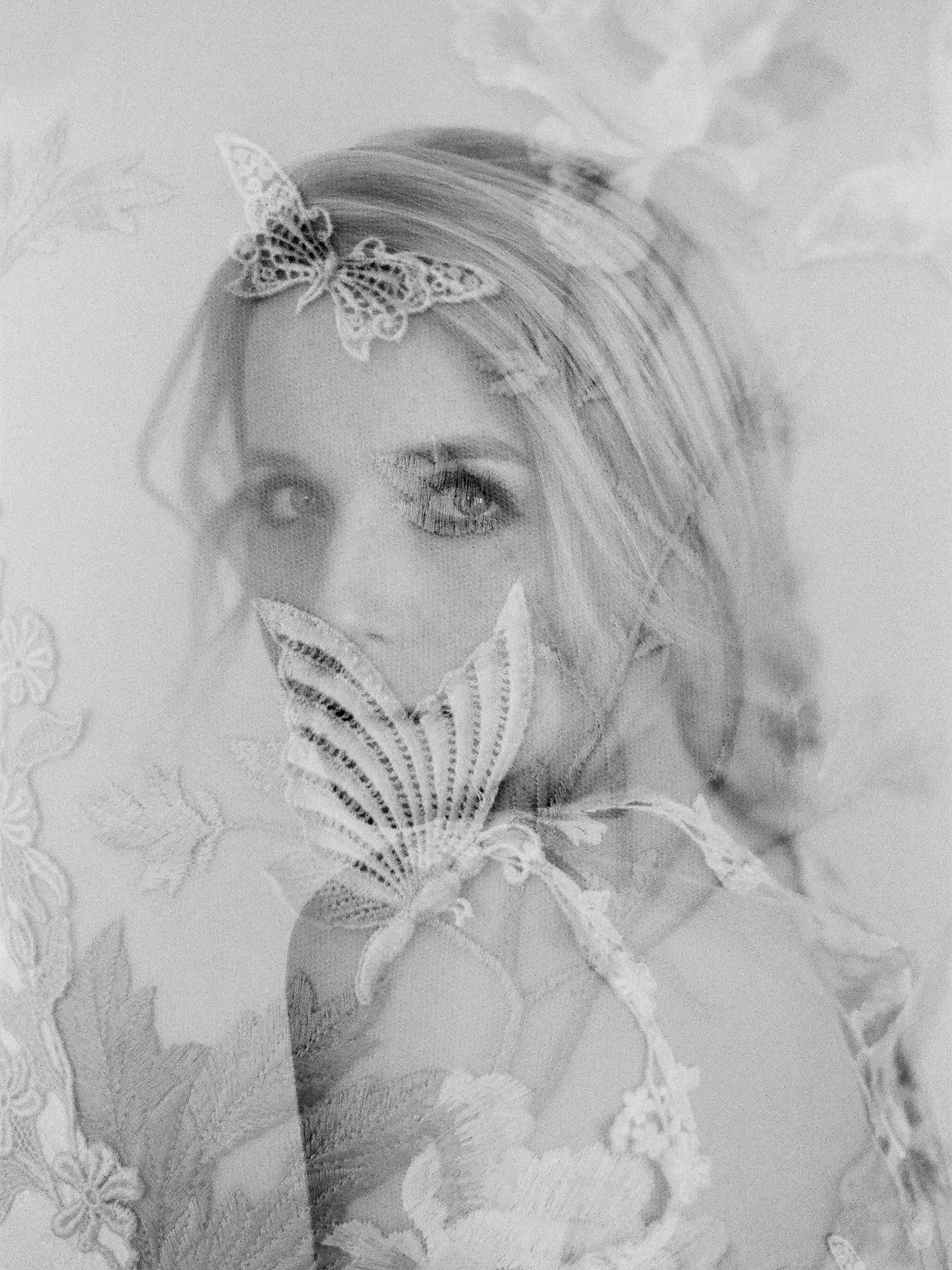 Brides face seen through applique veil with butterflies- photo by Jen Huang
