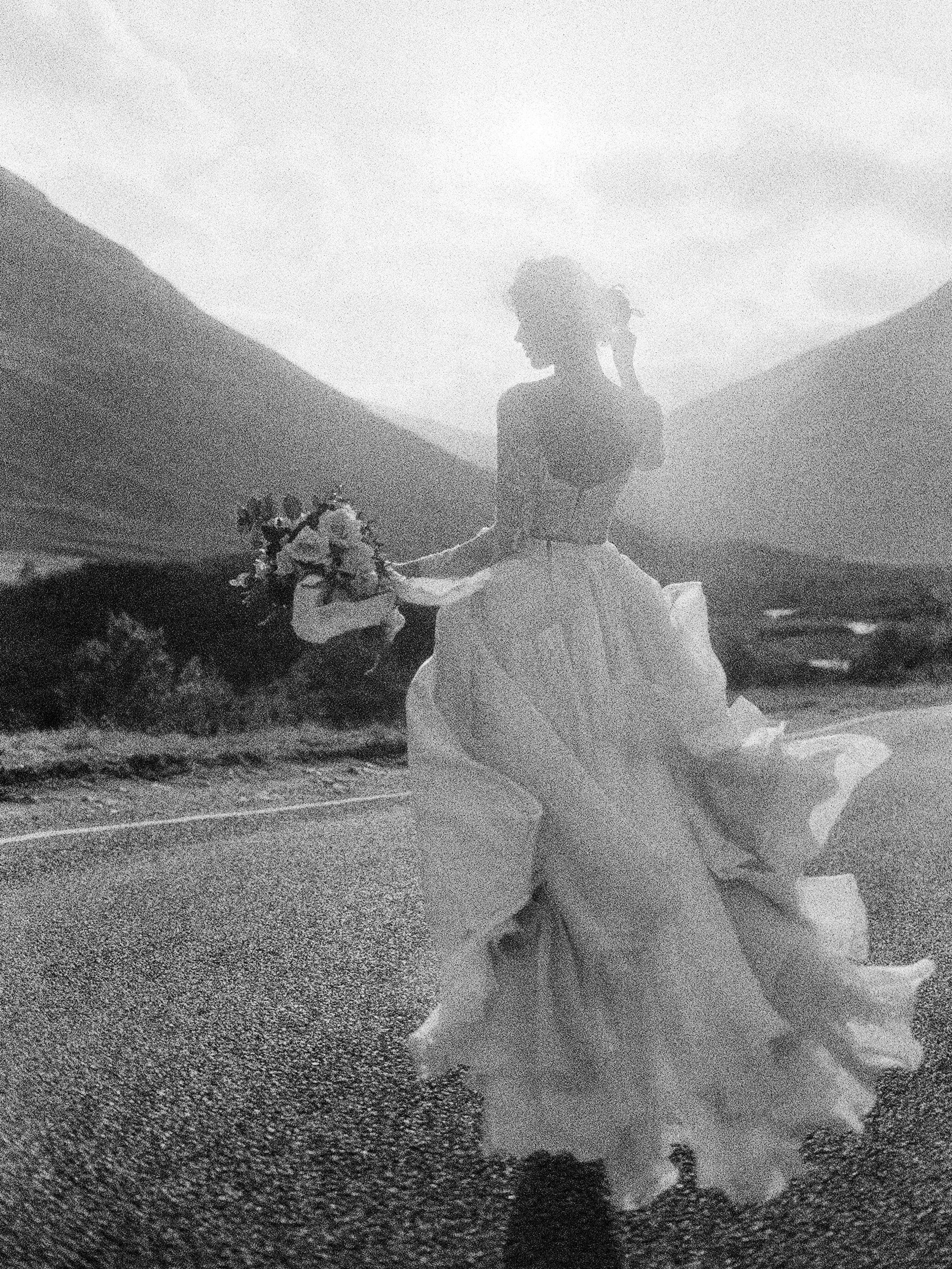 Ethereal back view of bride against mountains - photo by Jen Huang