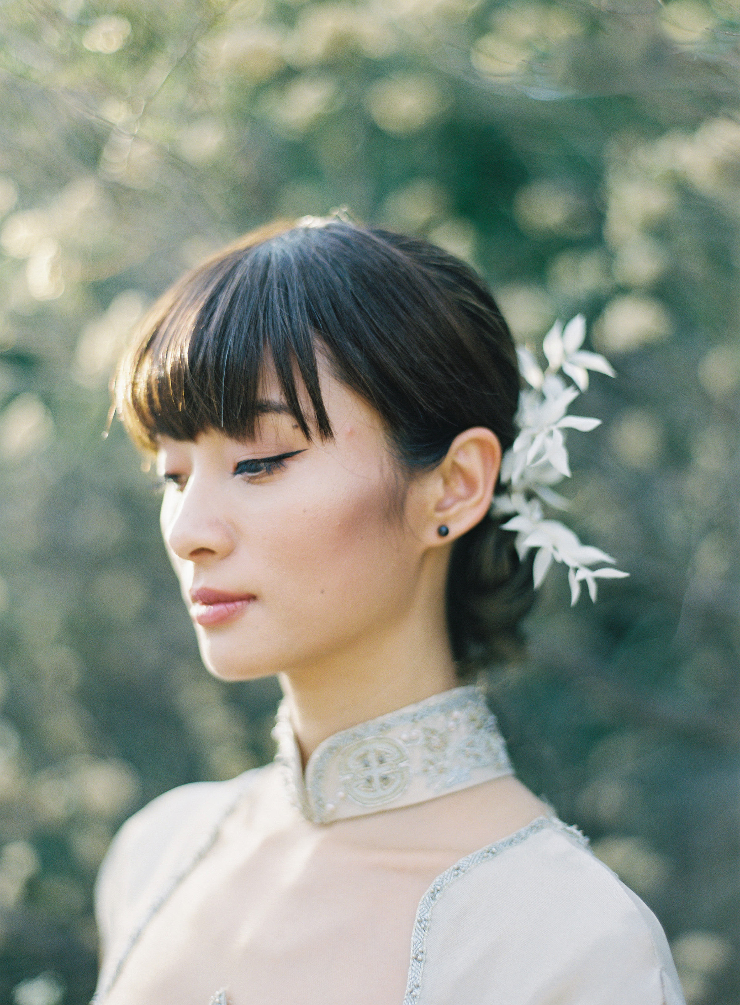 Three quarter profile bride with floral hair accessory - photo by Jen Huang