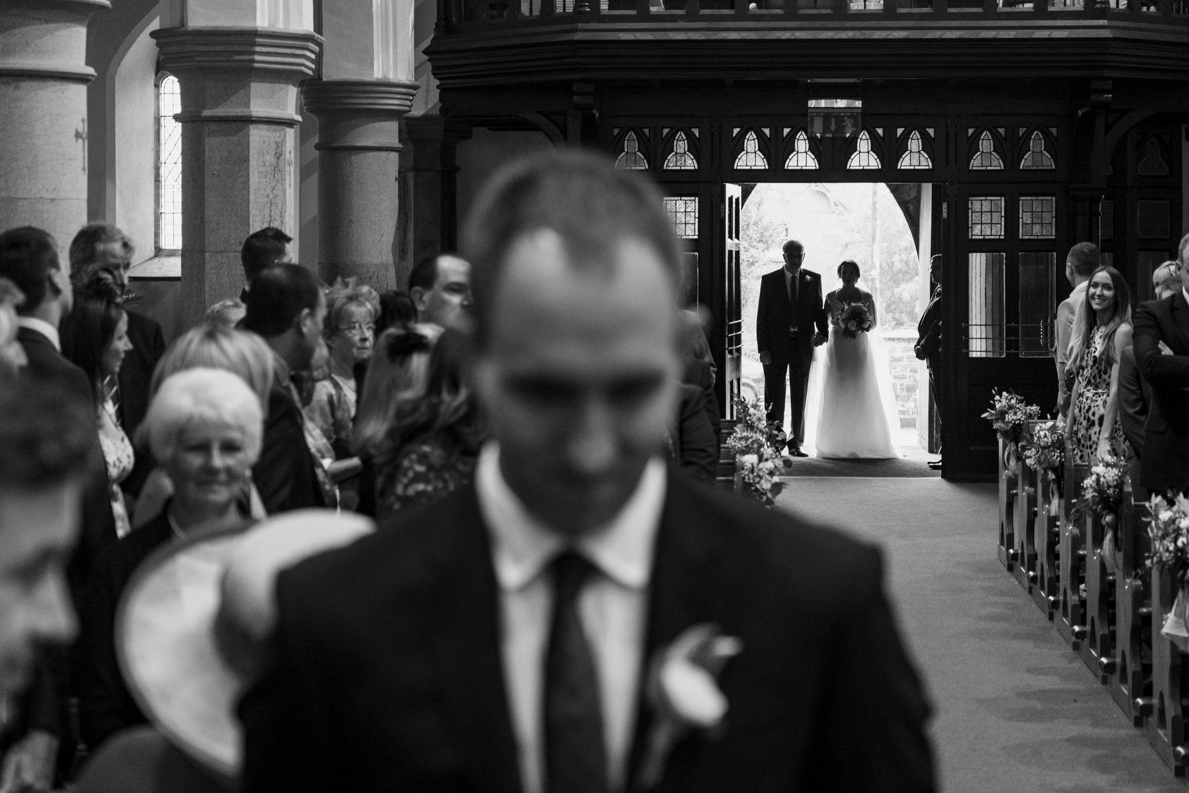 Bride enters church with father while groom waits at altar - photo by The Portrait Rooms