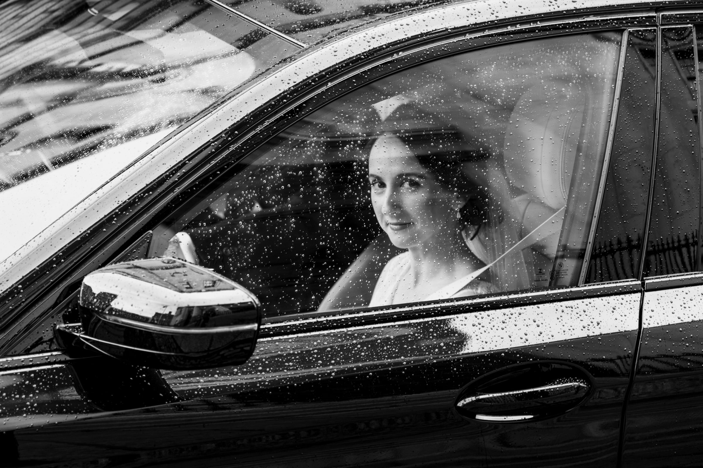 Bride in car seen through rain spattered window - photo by The Portrait Rooms