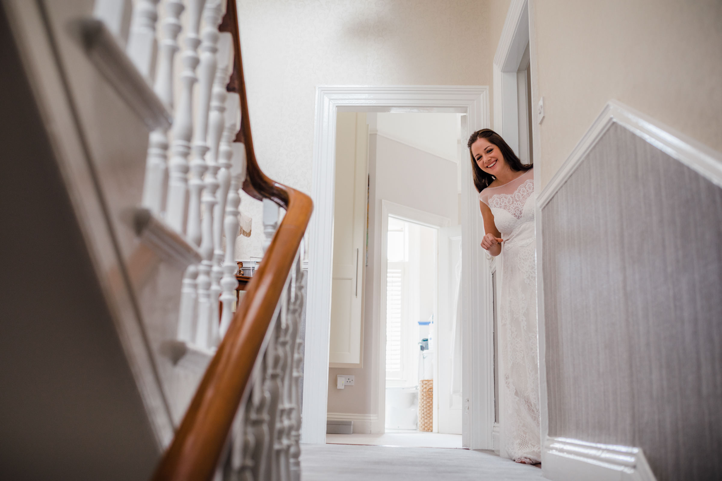 Bride peeks down the stairs - photo by The Portrait Rooms