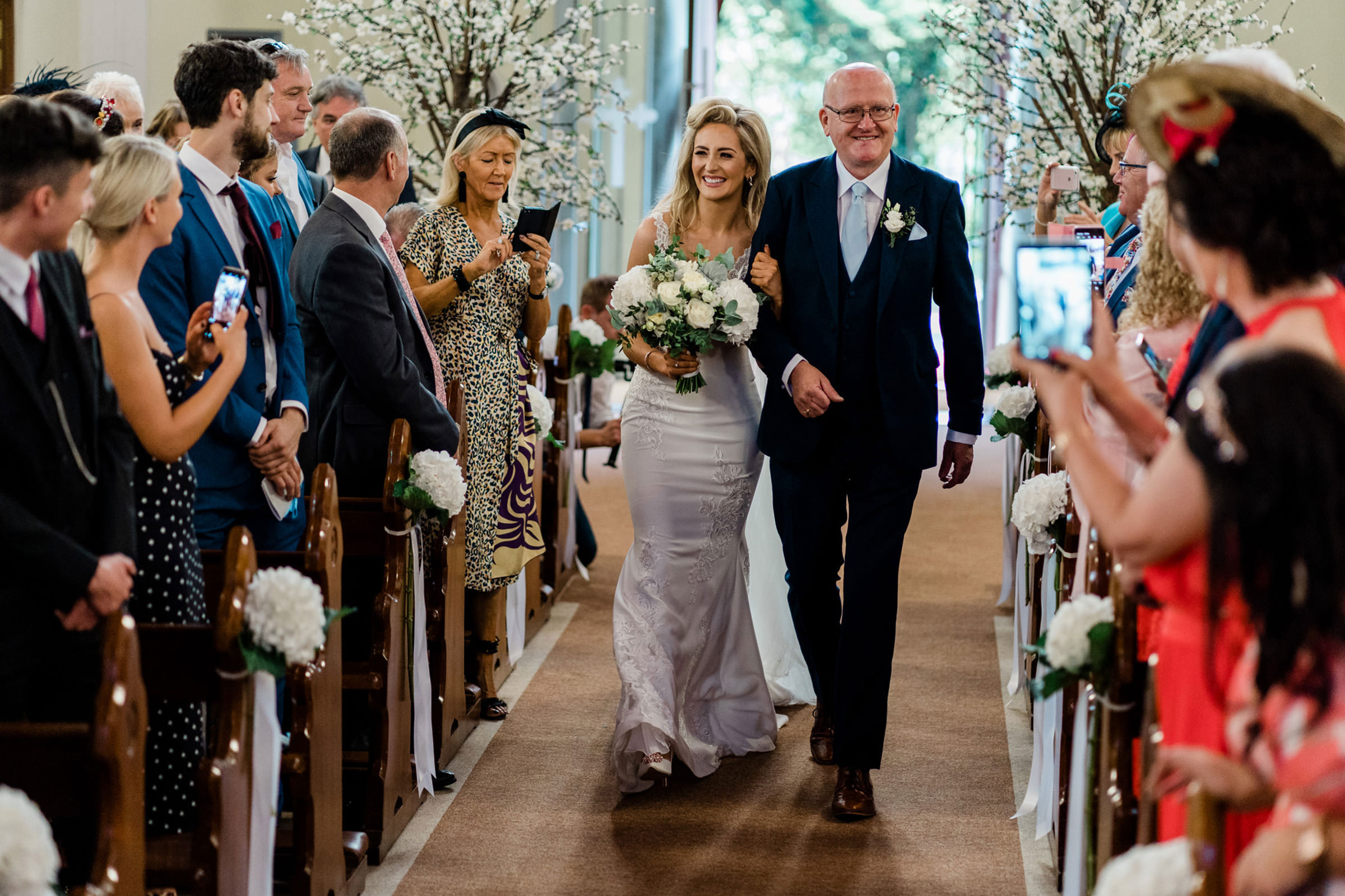 Bride walking down aisle with father - photo by The Portrait Rooms