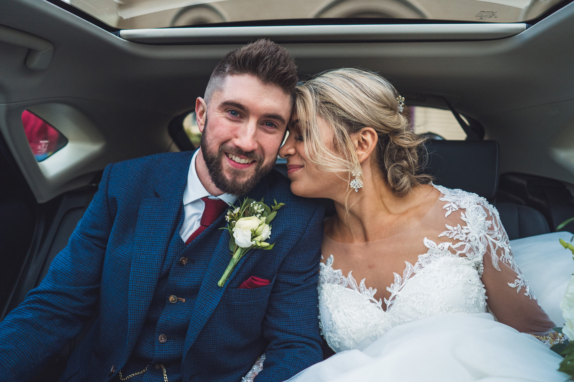 Couple snuggles in limo - photo by The Portrait Rooms