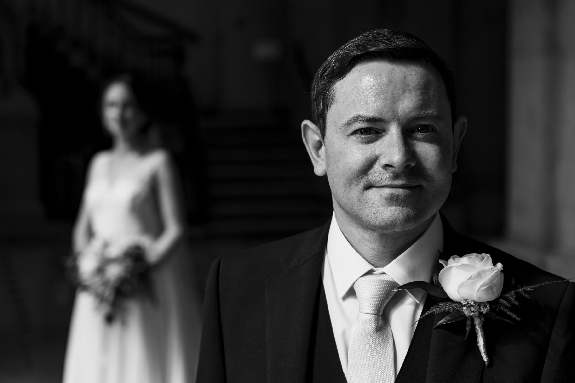 Groom portrait with bride in background - photo by The Portrait Rooms