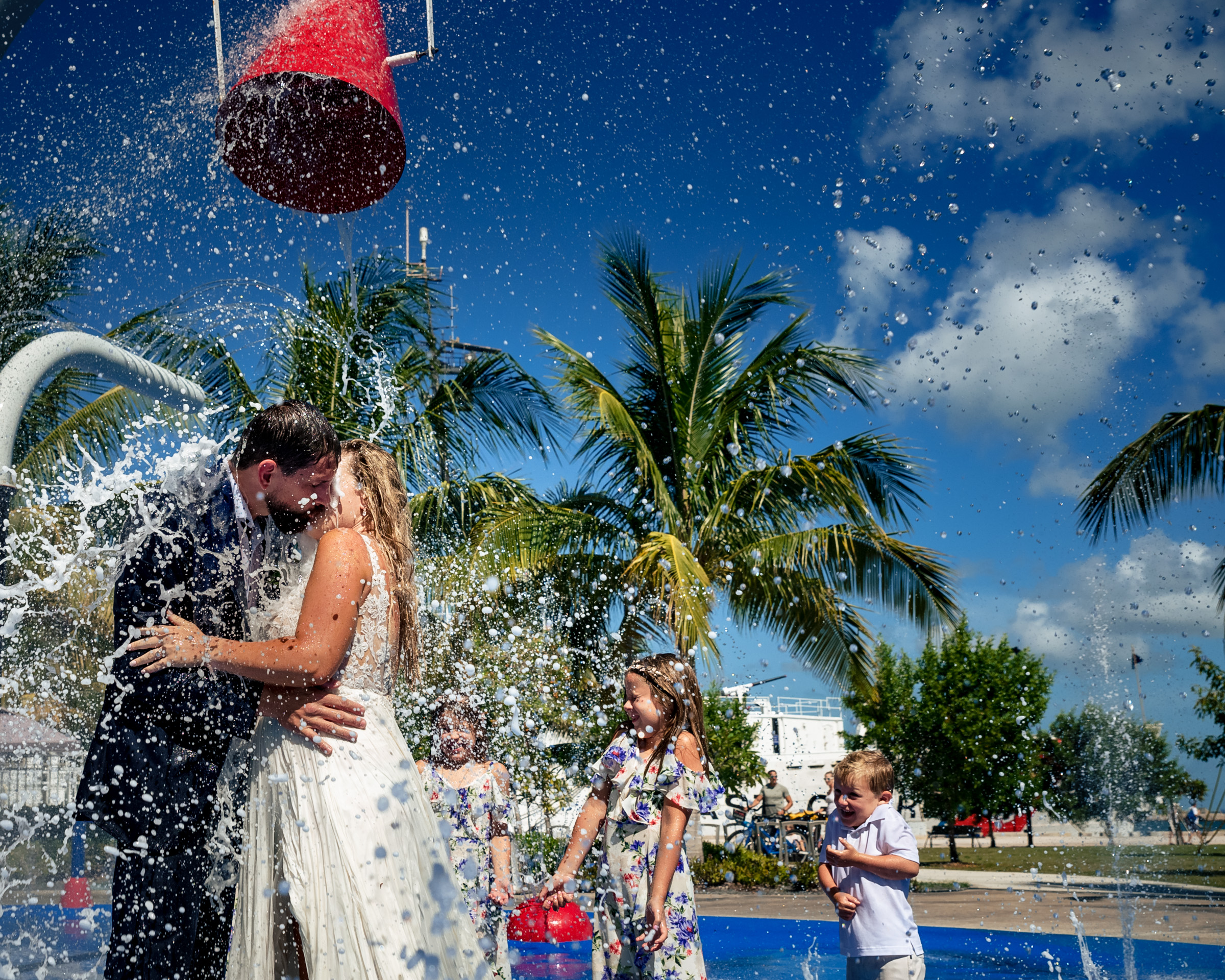 Couple kiss amid pool splashes - photo by Michael Freas Photography