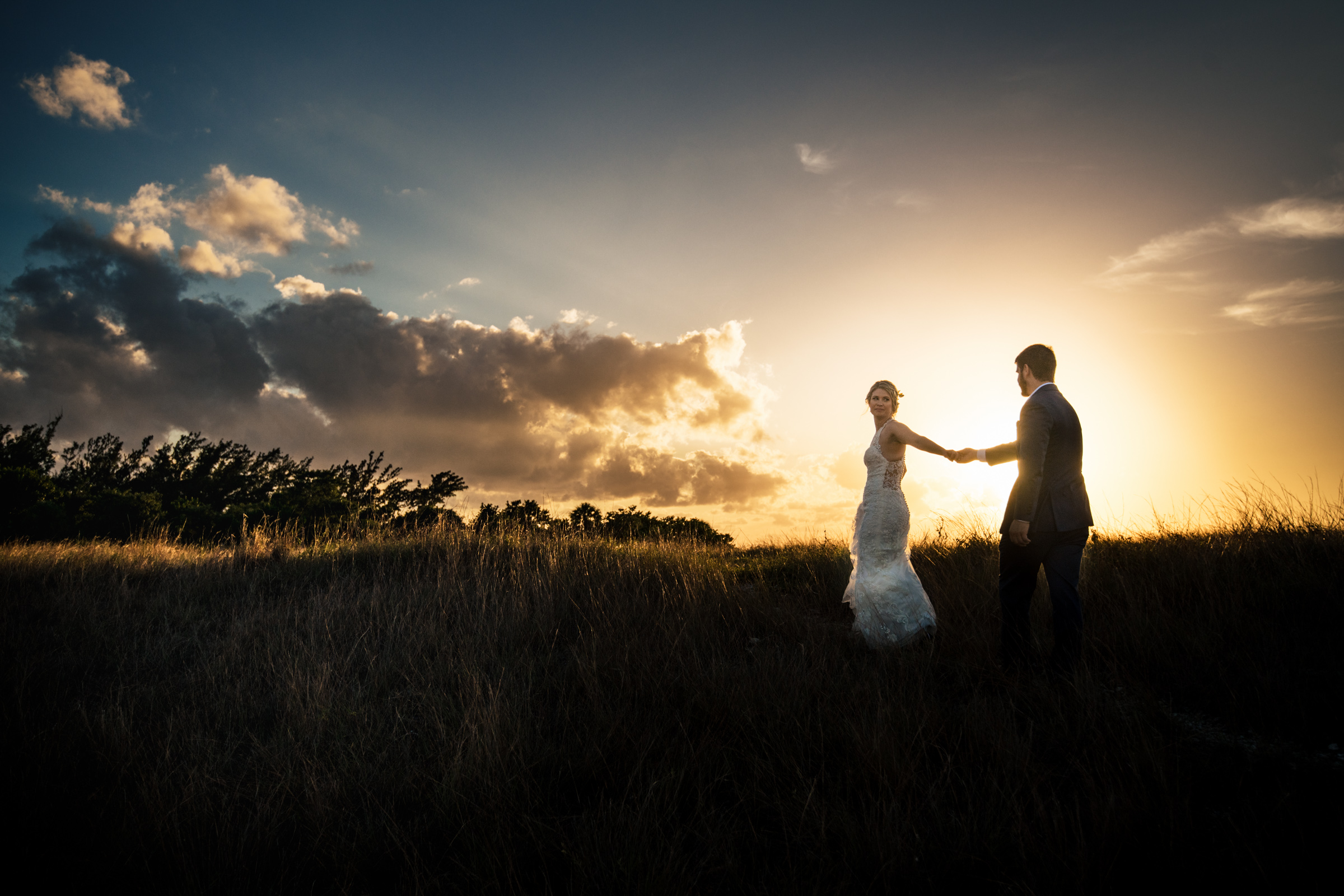 Bride leads groom across field during golden sunset  - photo by Michael Freas Photography - Connecticut