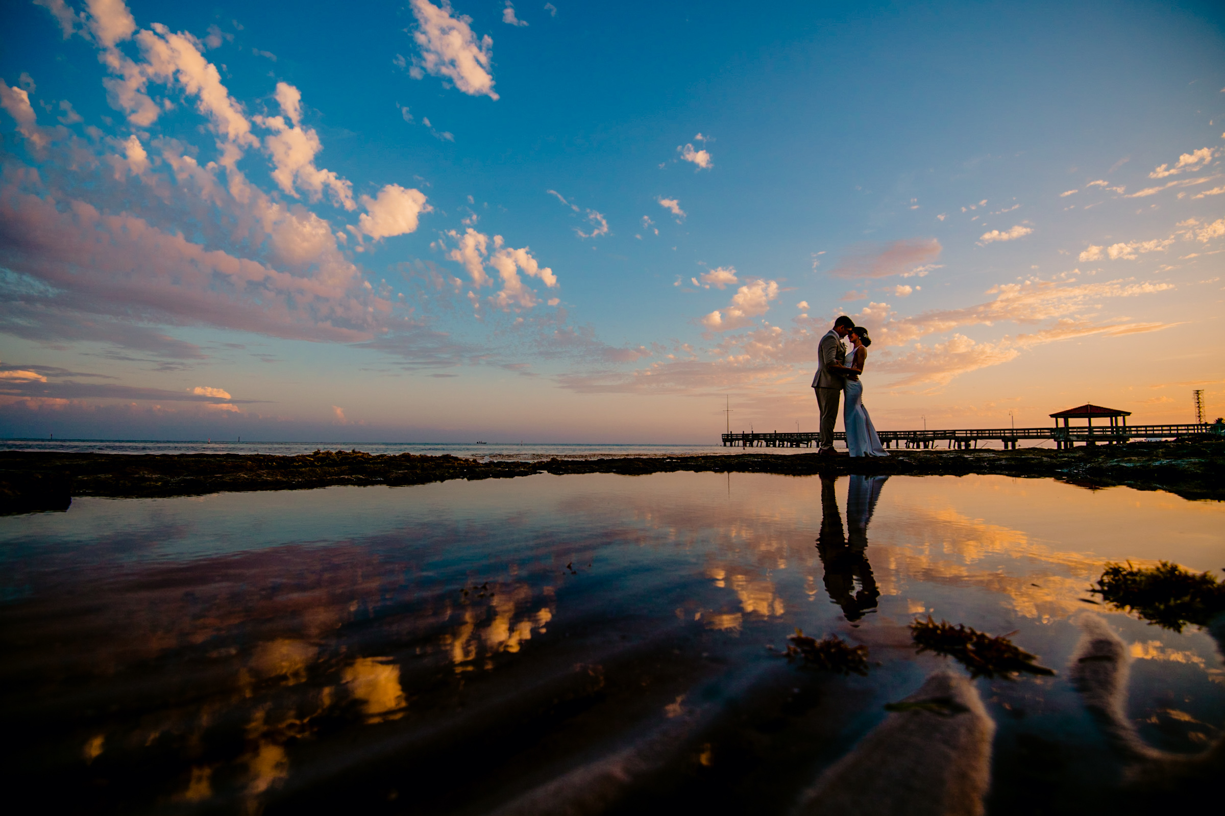 Couple against sunset reflected in water - photo by Michael Freas Photography - North Carolina
