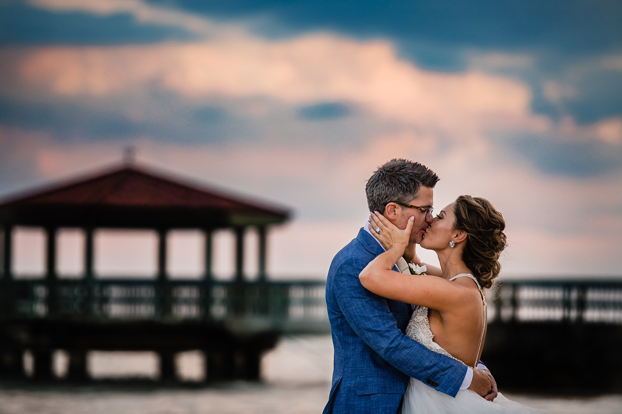 Couple kissing on the beach in front of gazebo  - photo by Michael Freas Photography - North Carolina