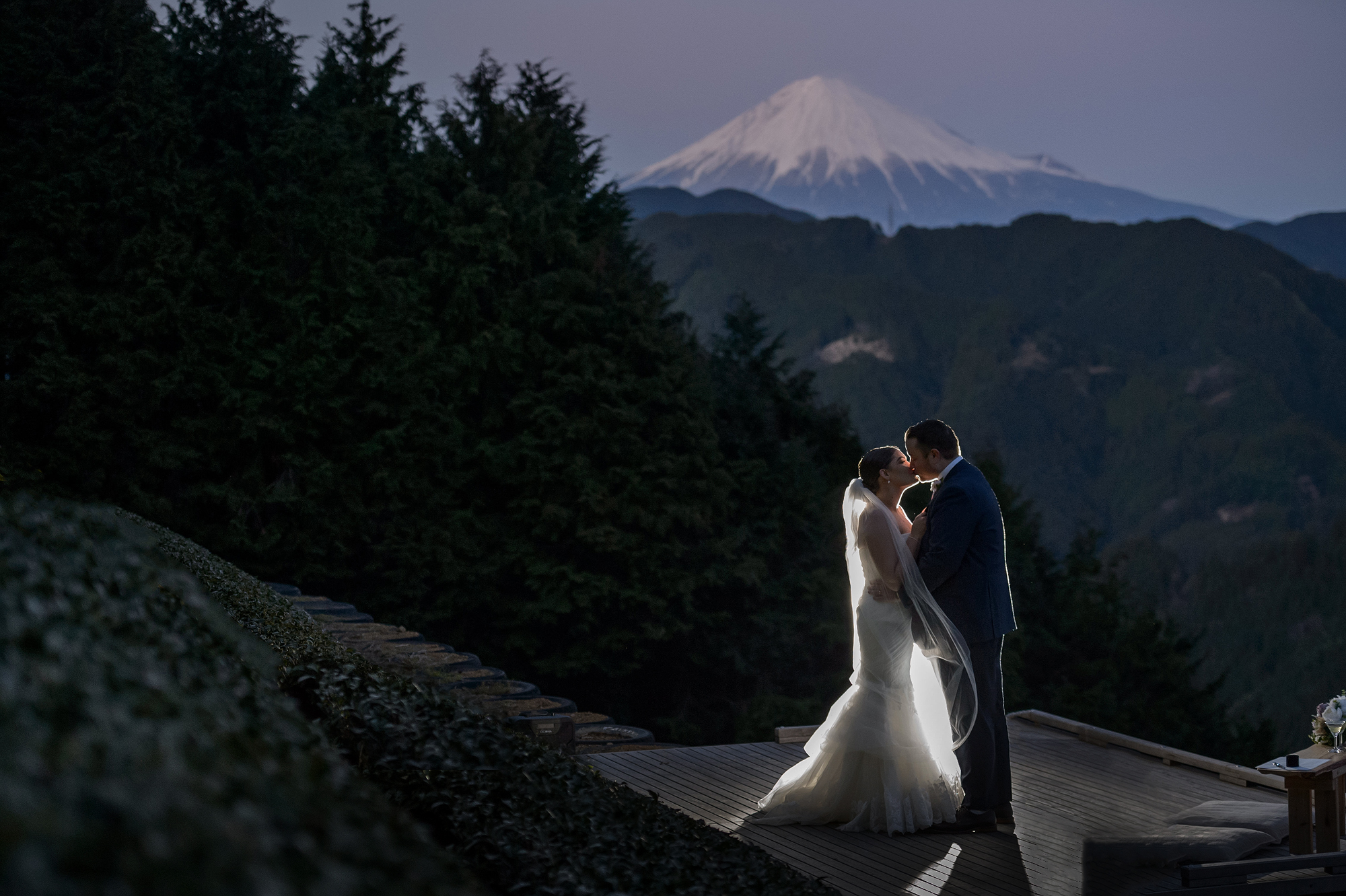 Bride and groom kiss against Mount Fuji - photo by 37 Frames