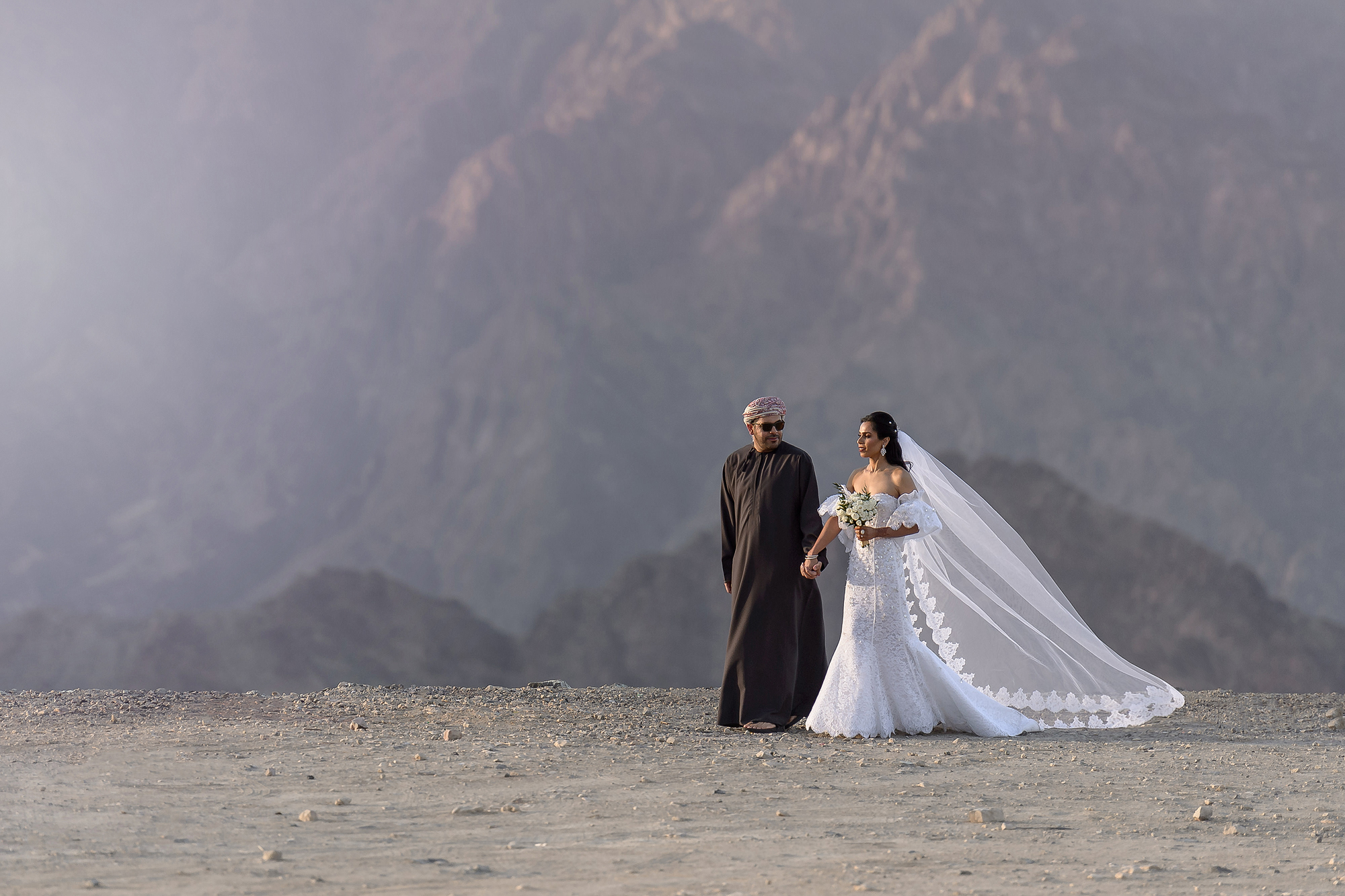 Bride and groom walking against mountains, photo by 37 Frames