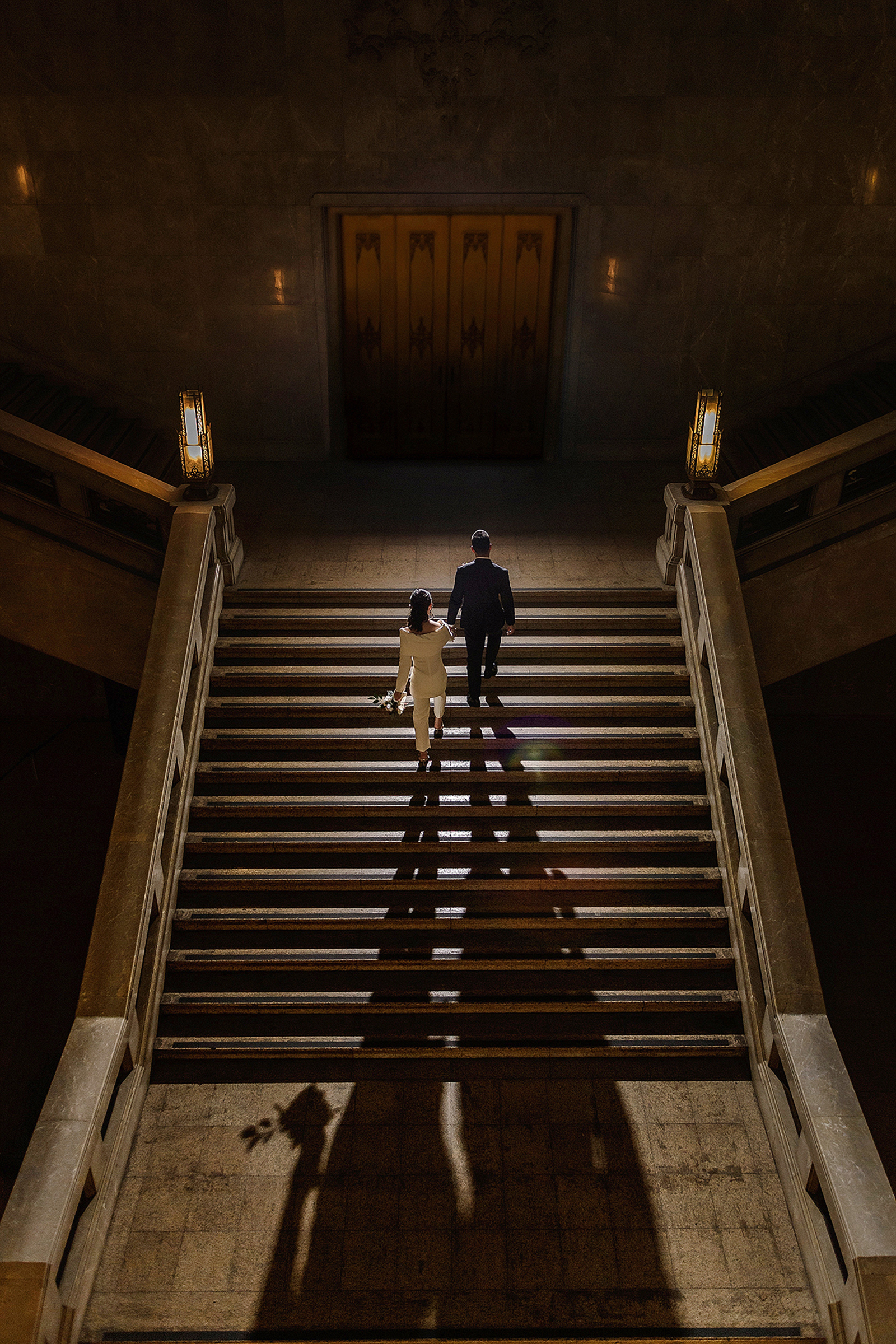 Long shadows trail couple up staircase - photo by 37 Frames