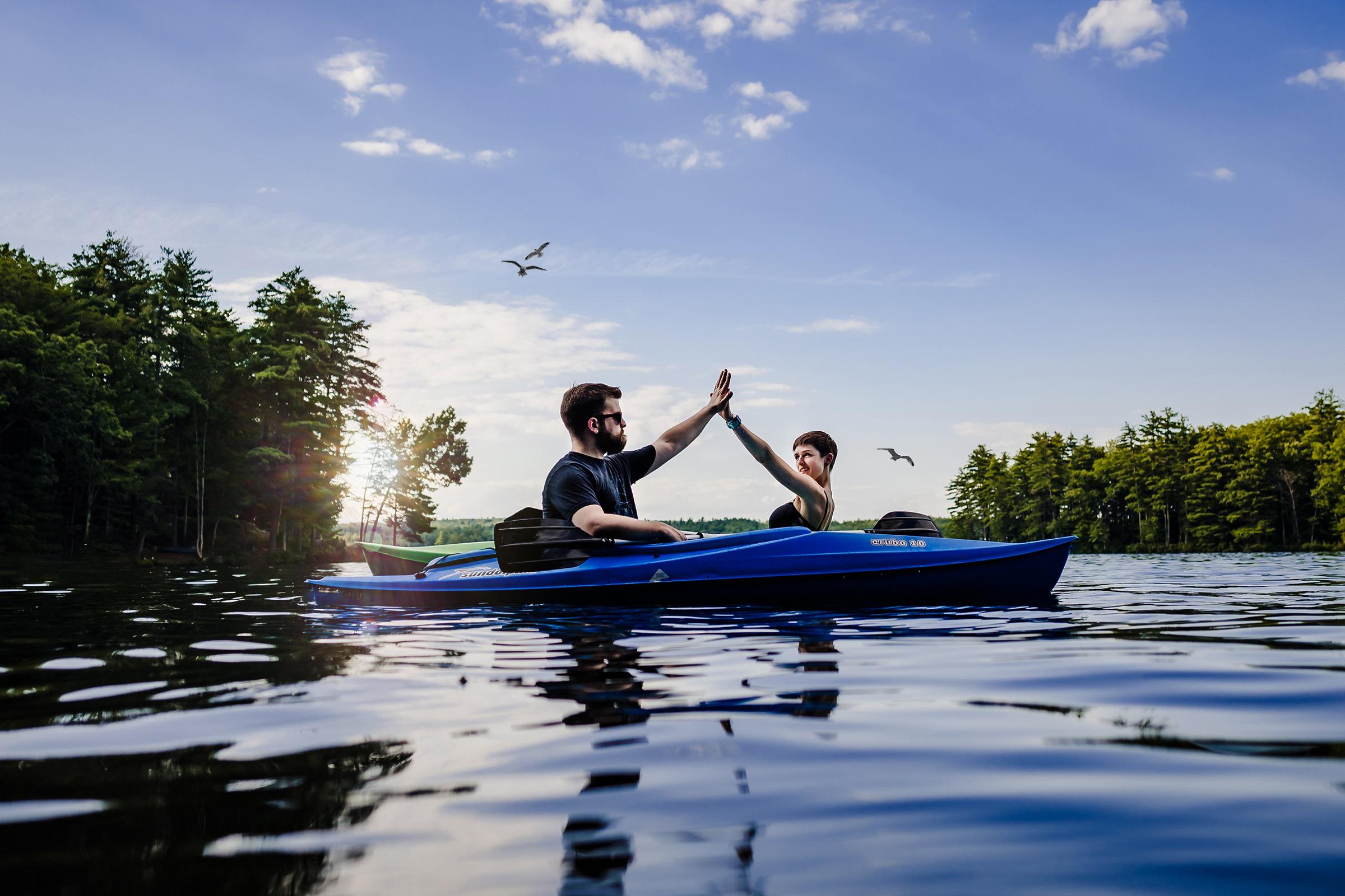 Couple in canoe high fiving - photo by Meraki Portrait