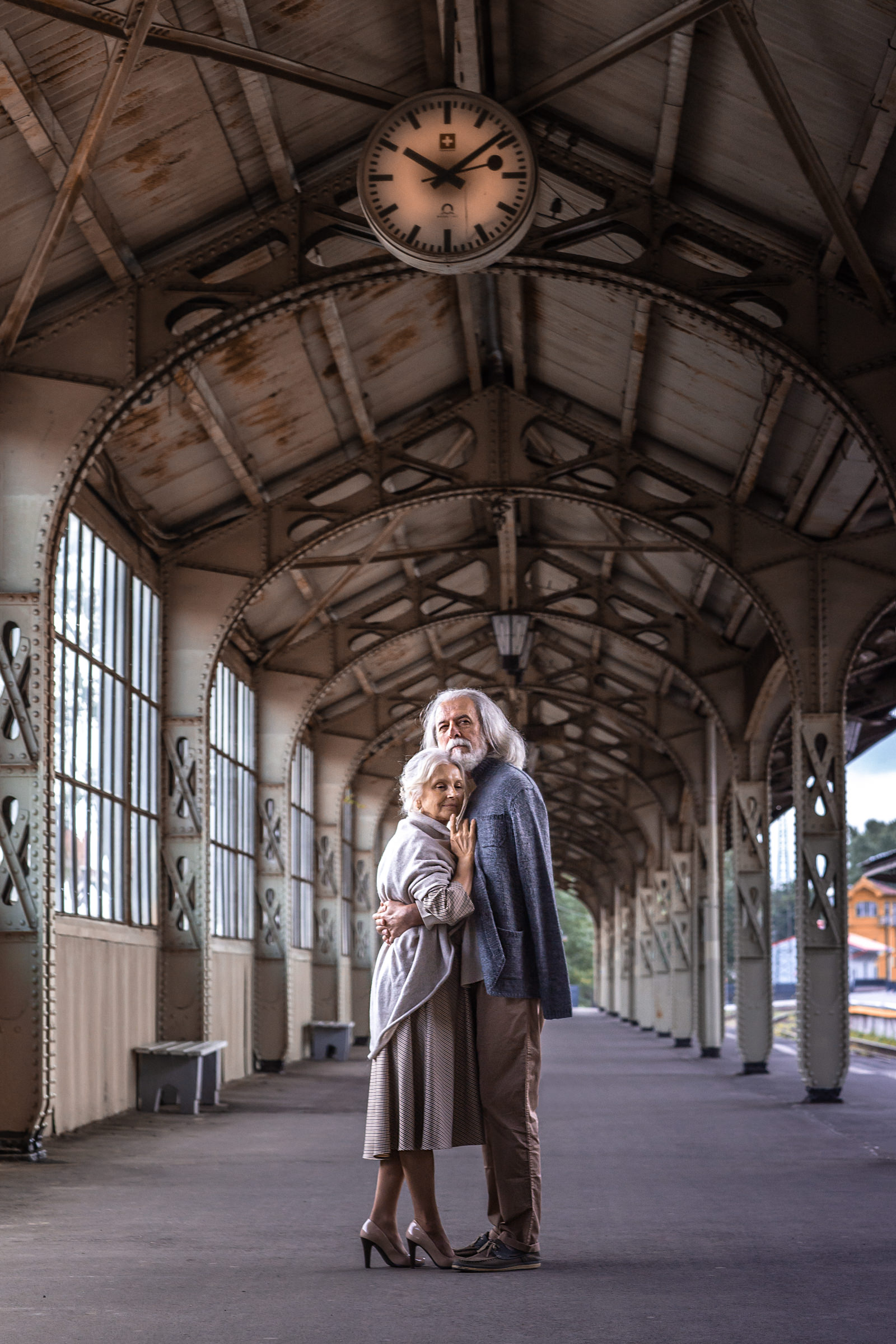 Older couple in train station underneath clock - photo by Bagrada Photos