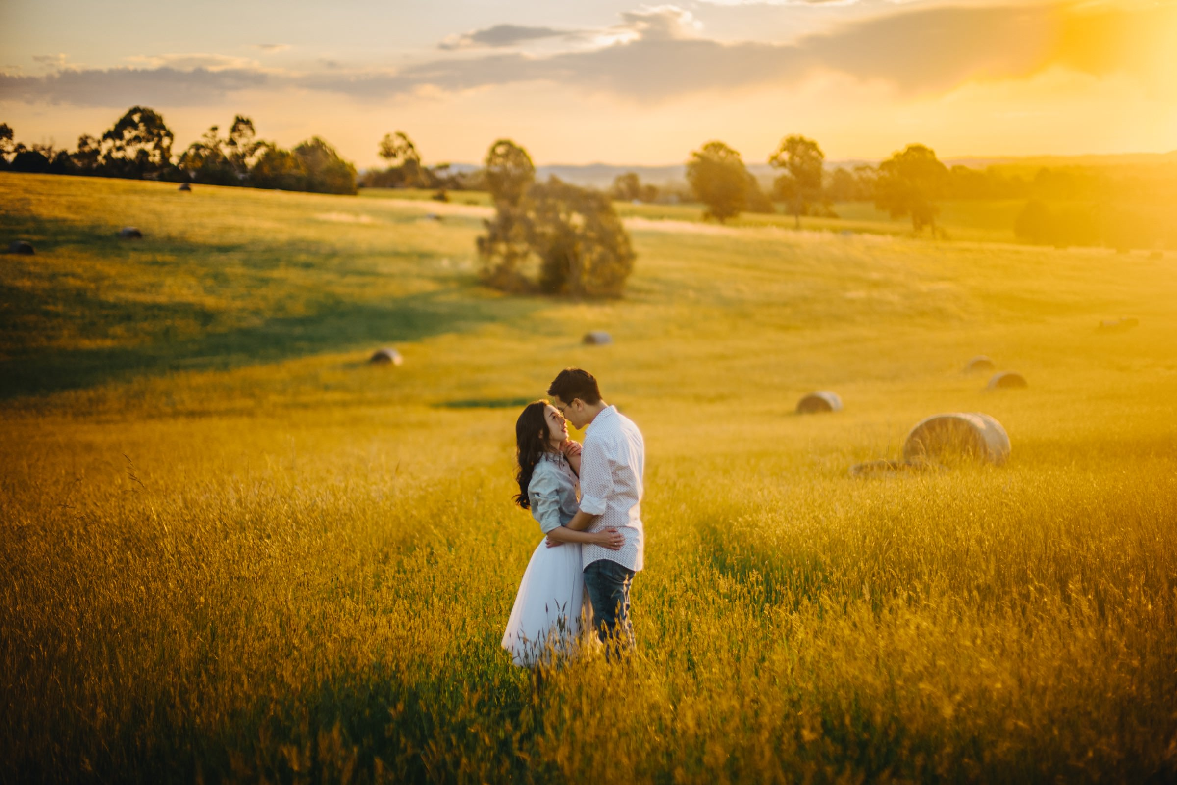 Couple in golden field of grass and hay rolls - photo by Feztography