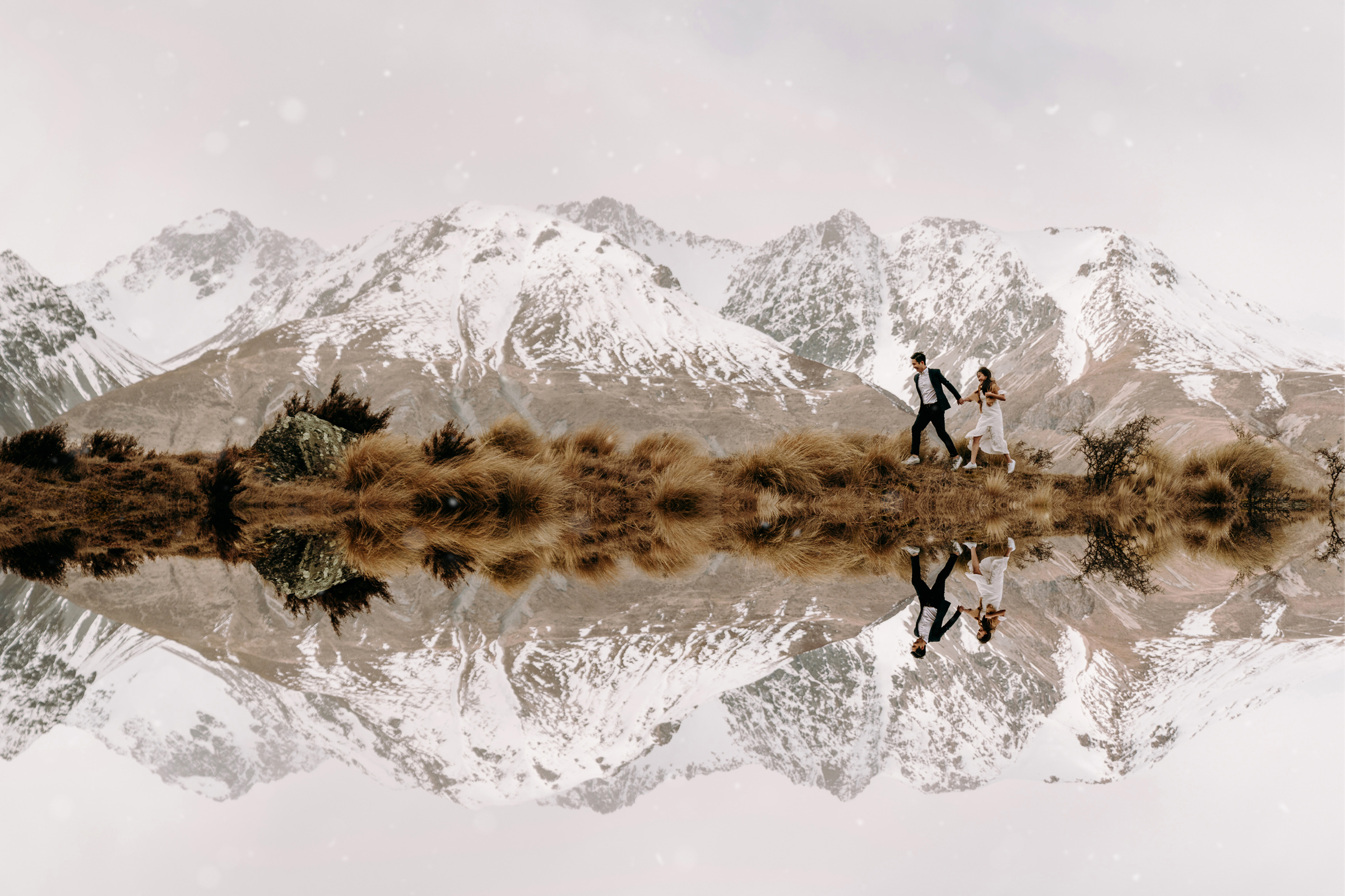 Couple walking against snowy mountains - photo by Tinted Photography
