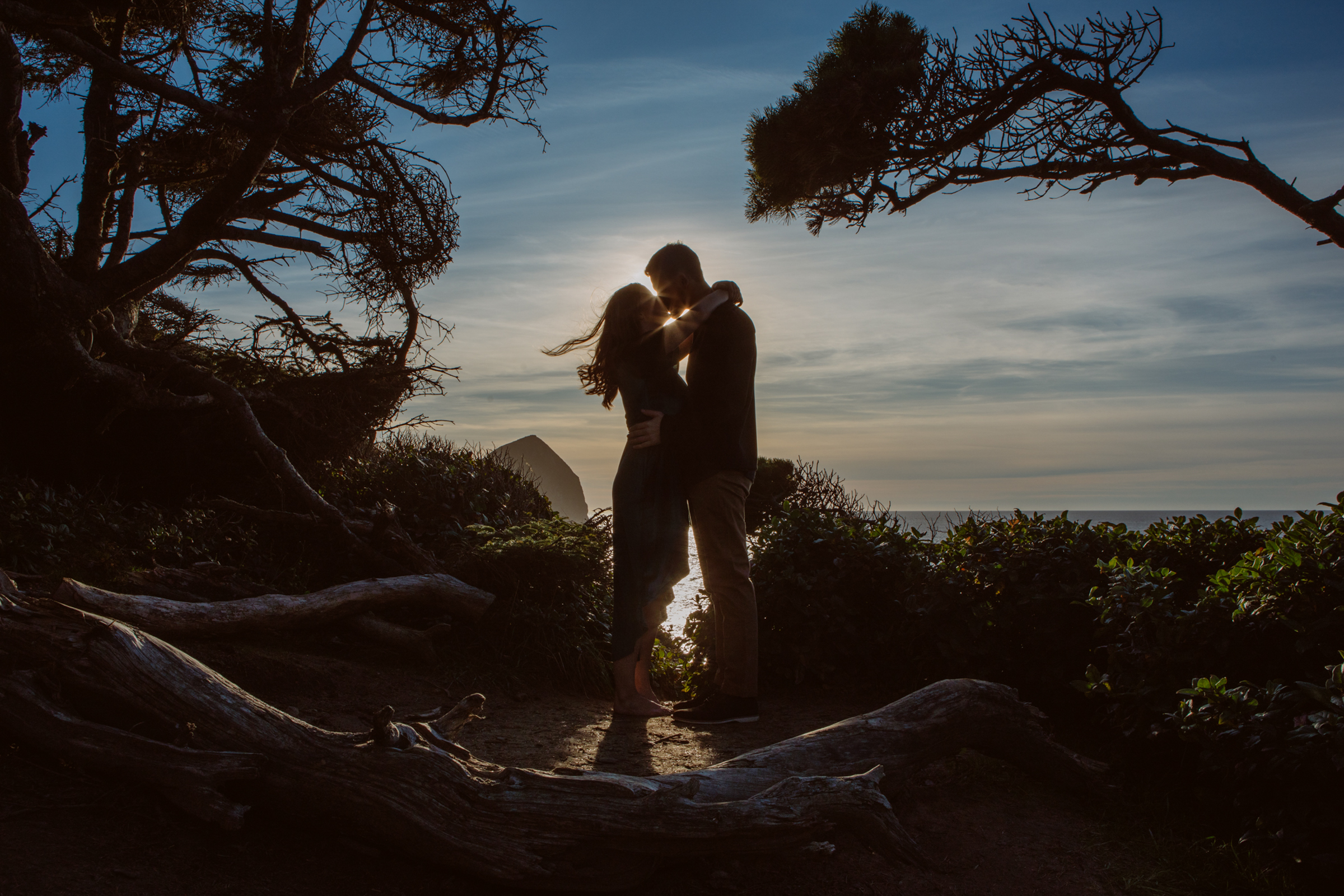 Engagement kiss on stormy beach setting - photo by Jessica Hill Photography