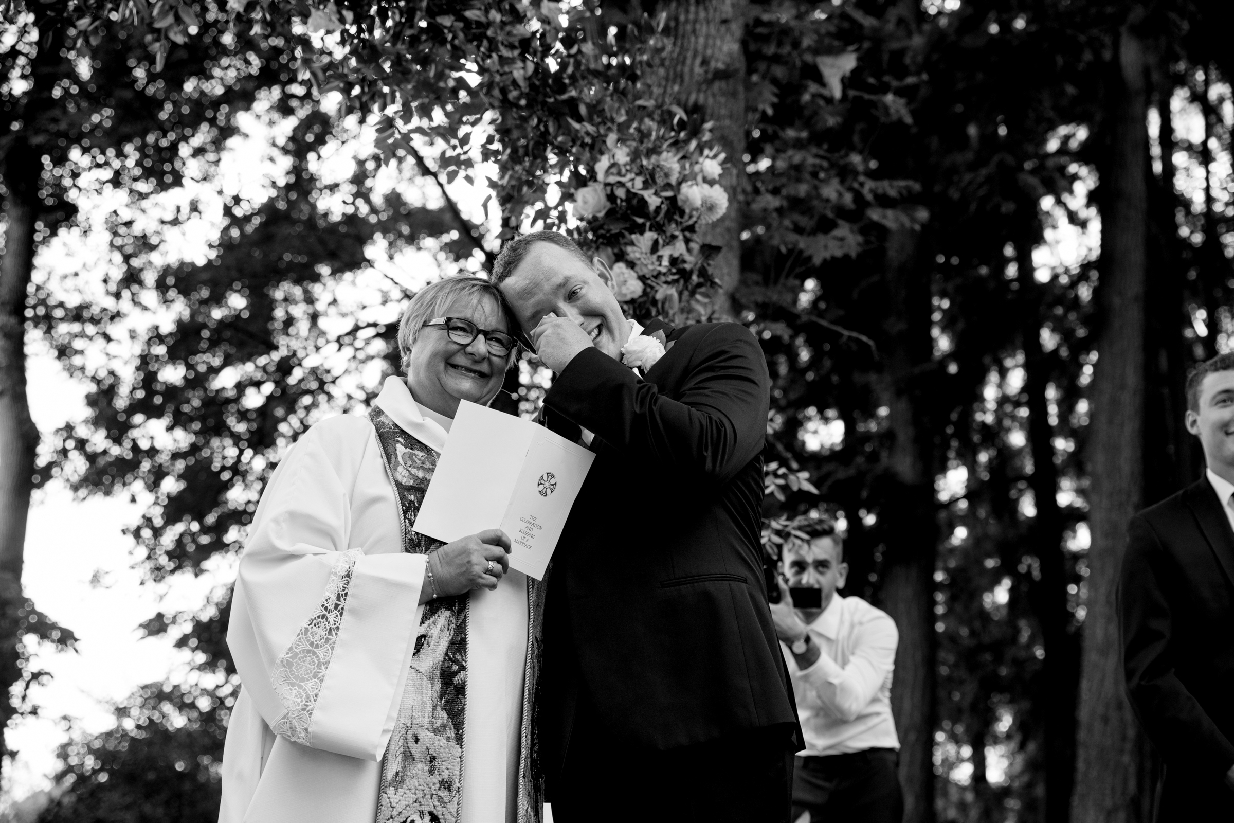 Officiant smiles as groom sheds a tear - photo by Jessica Hill Photography