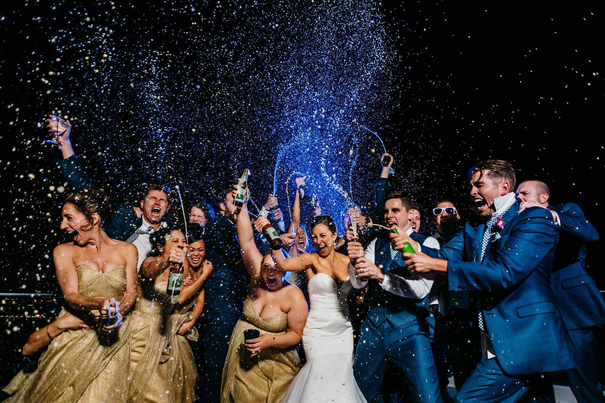Wedding party celebrating with popping champagne - photo by Ken Pak Photography