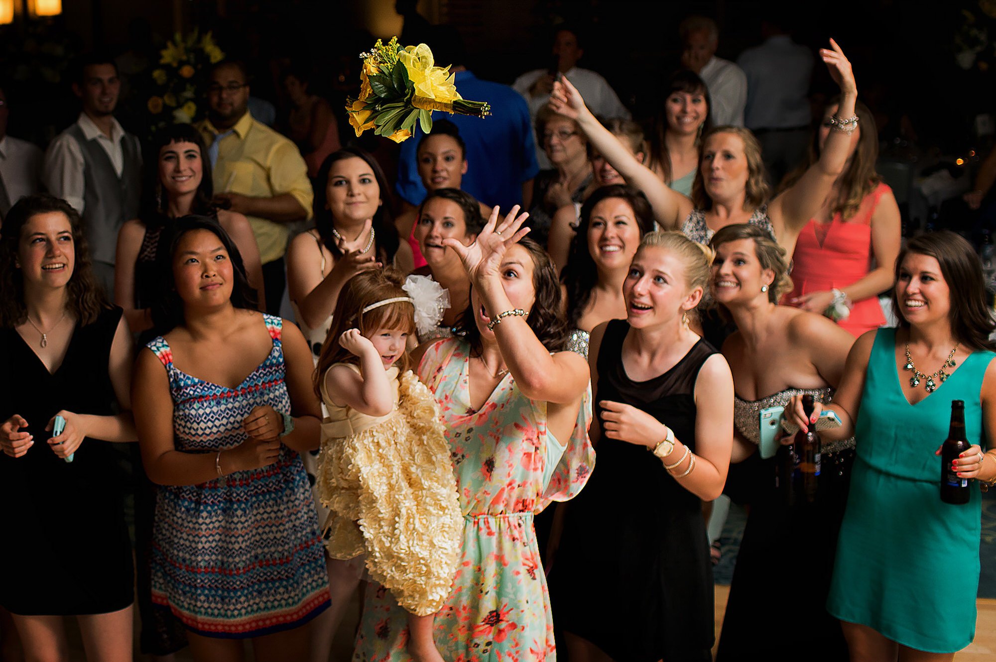 Woman holding little girl catches bouquet - photo by Ken Pak Photography