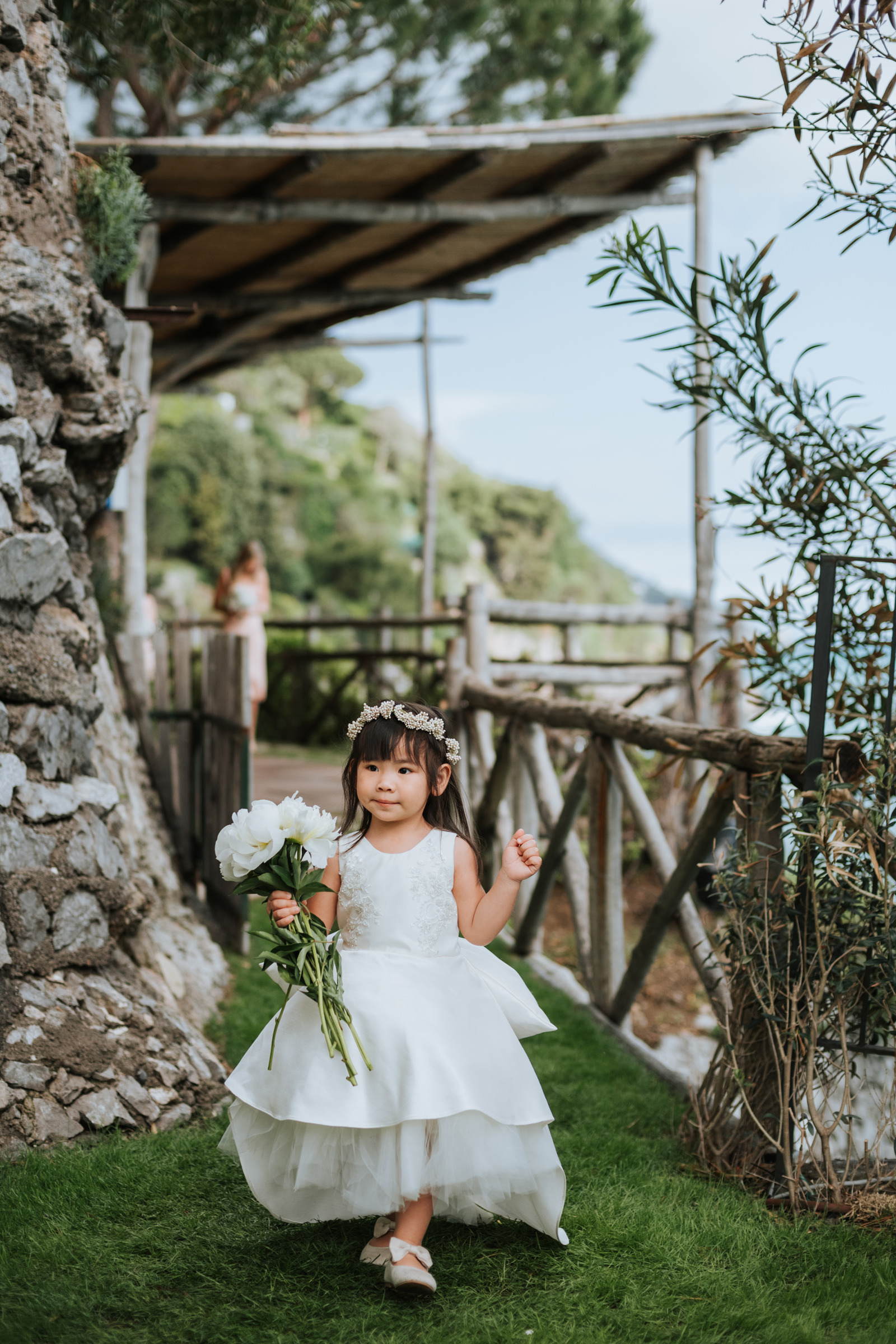 Small flower girl walking with large bouquet - photo by Mun Keat Studio