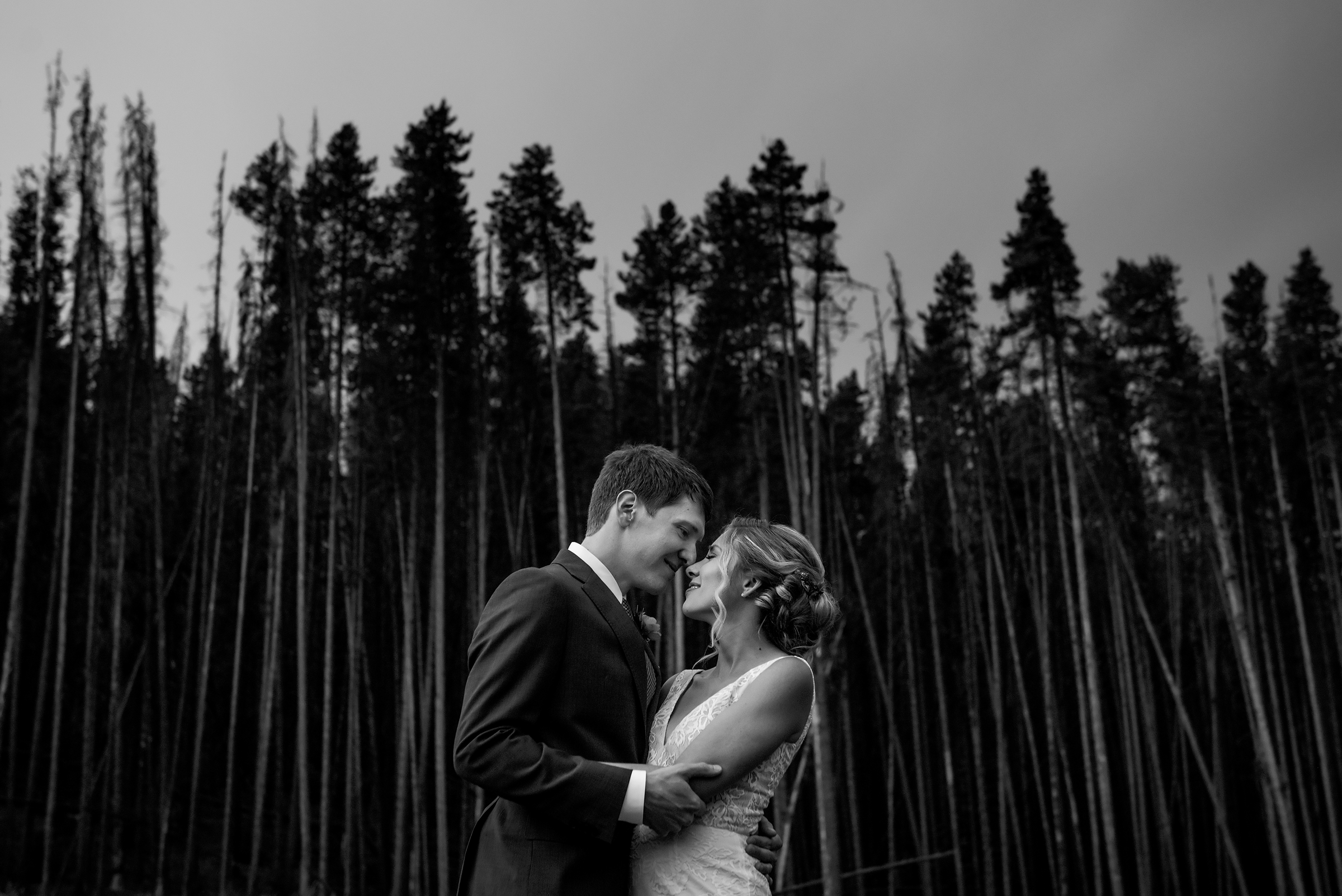 Couple embrace against forest backdrop - photo by Morgan Lynn Photography