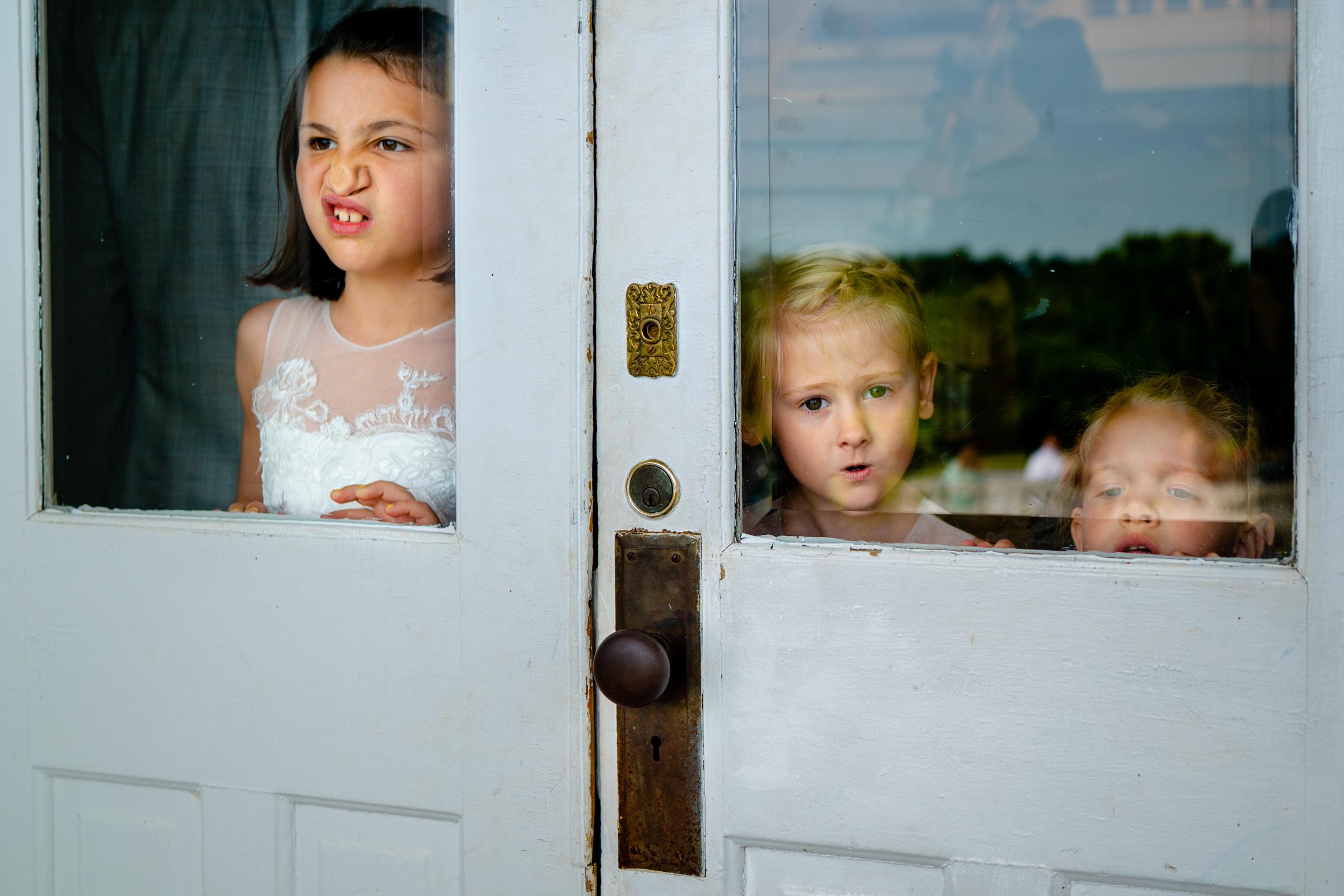 Kids looking through glass door photo by Bee Two Sweet