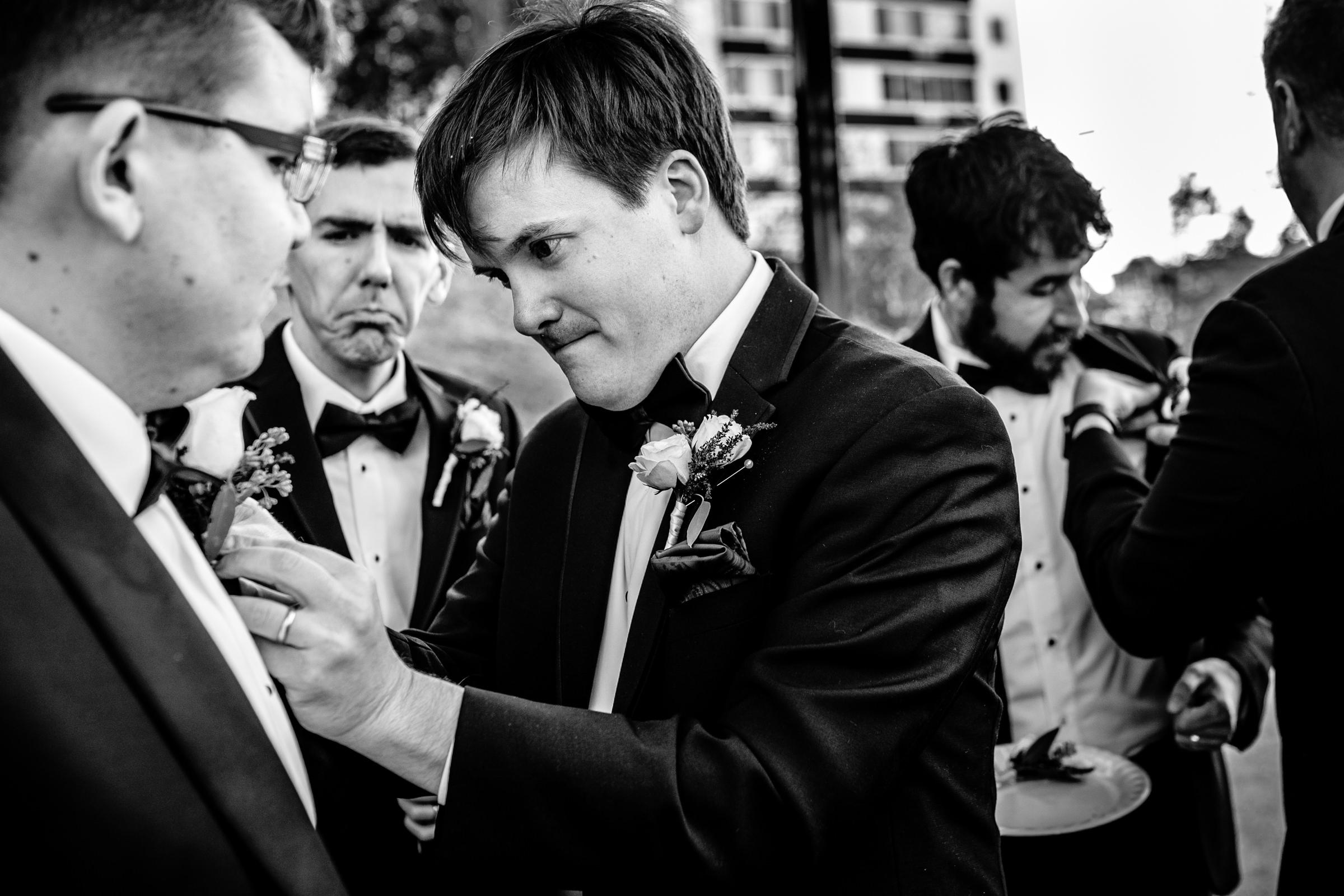 Groomsmen put on boutonnieres- photo by Bee Two Sweet