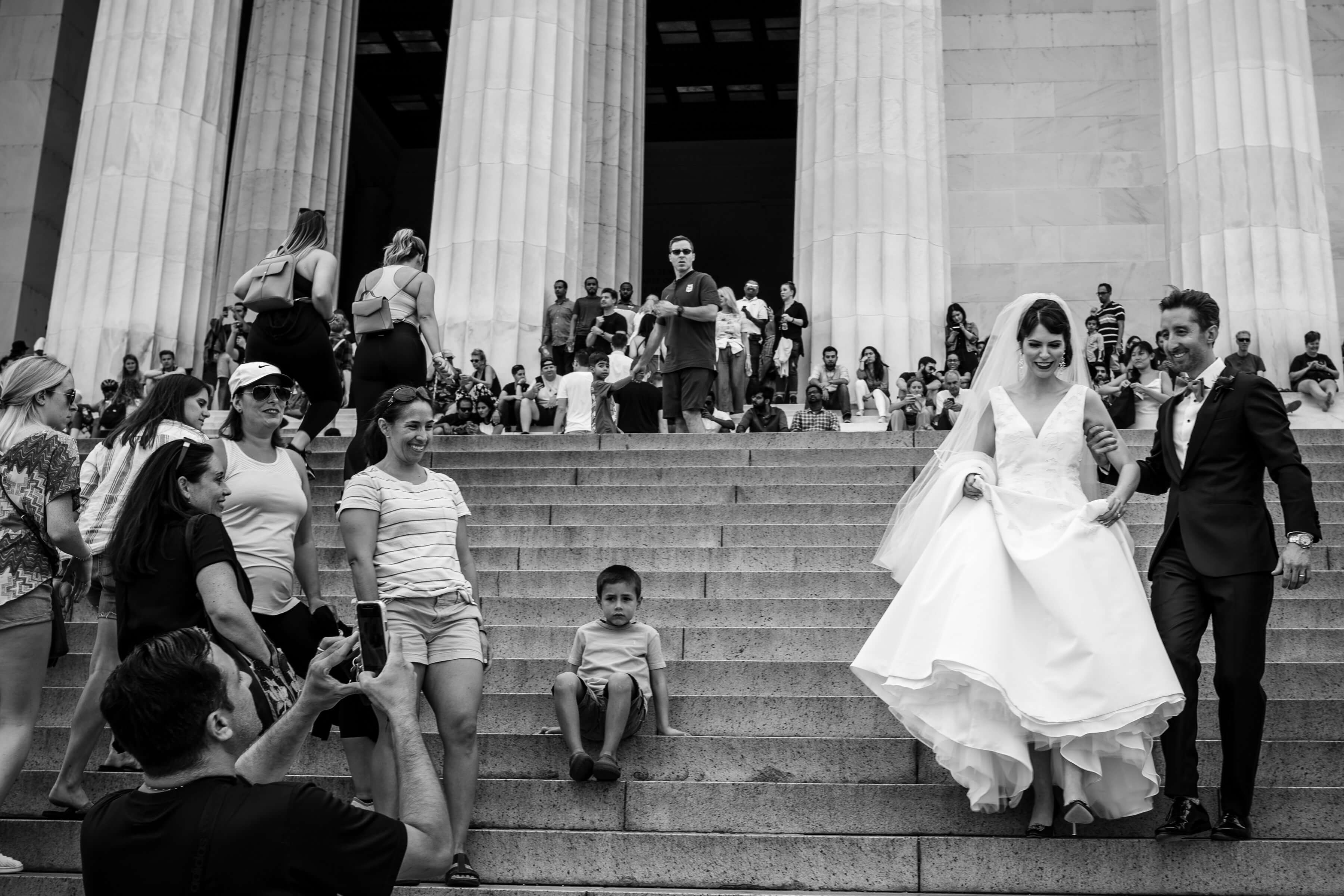 Couple descending iconic steps against onlookers - photo by Bee Two Sweet
