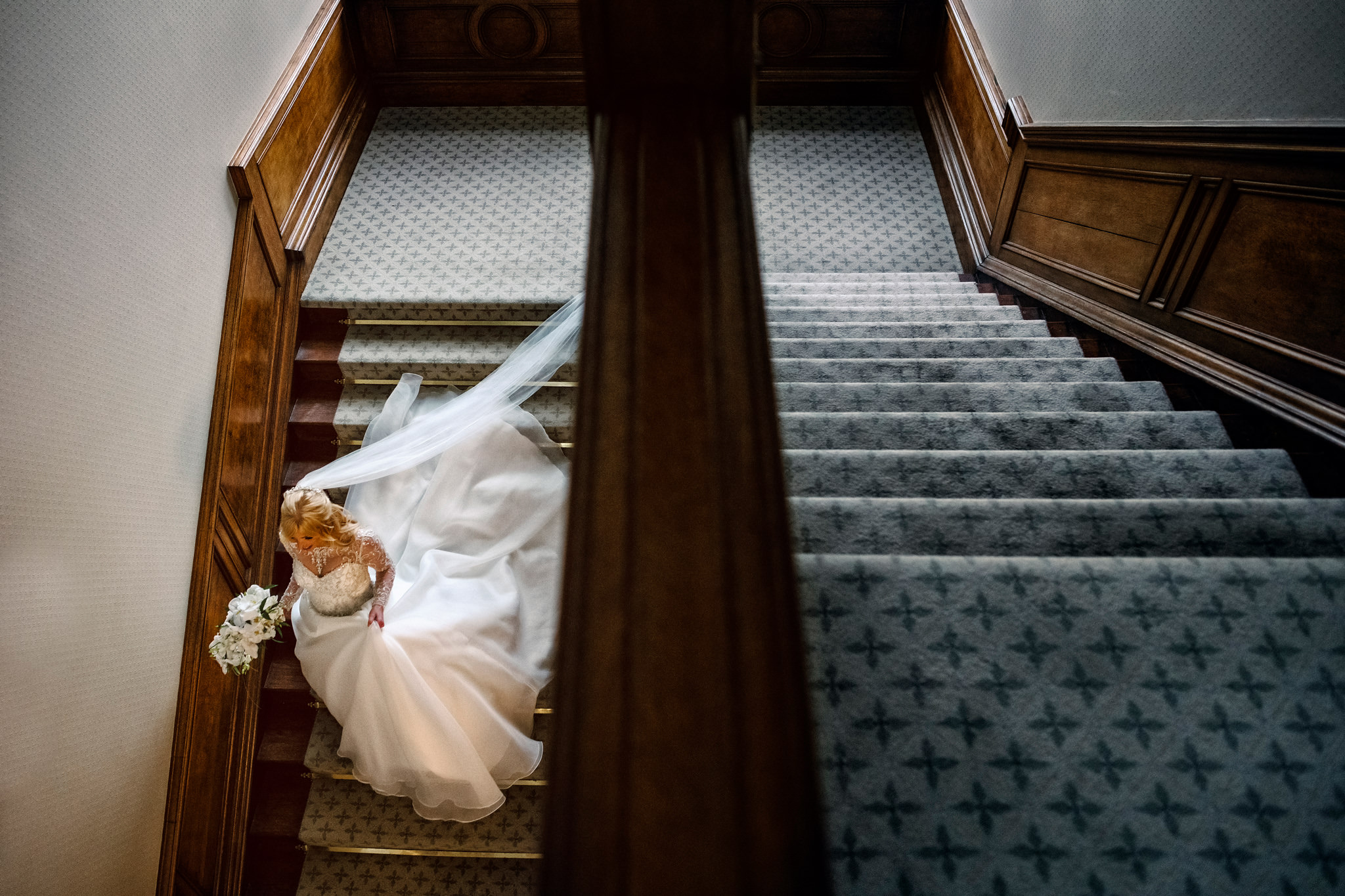 Bride descends stairway with chiffon dress and veil - photo by Rich Howman