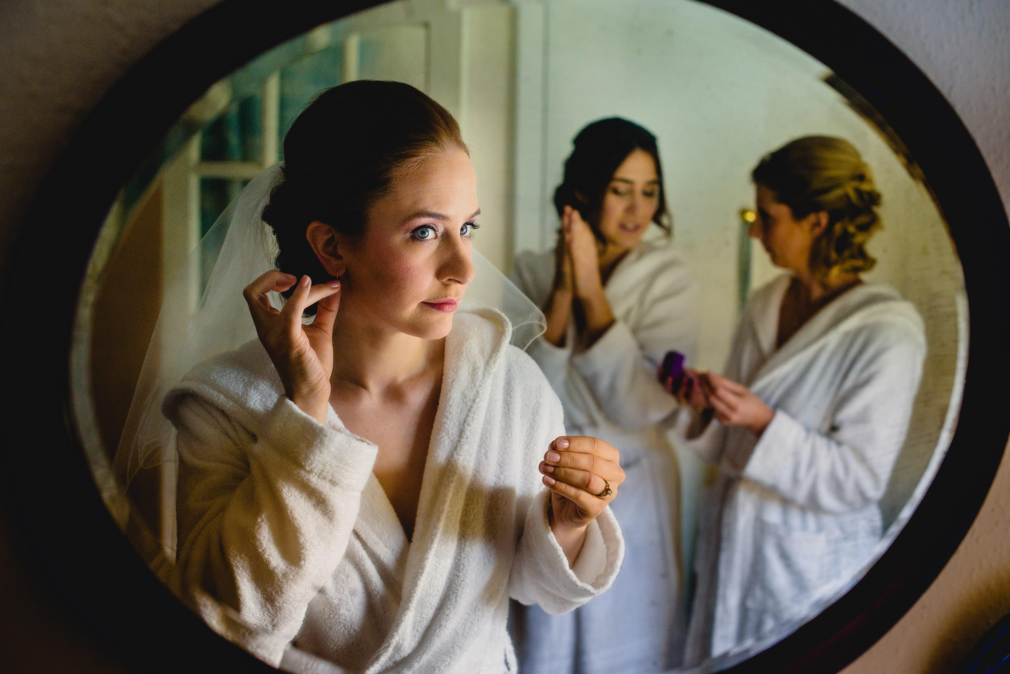 bride fixes her earring in mirror - photo by Rich Howman