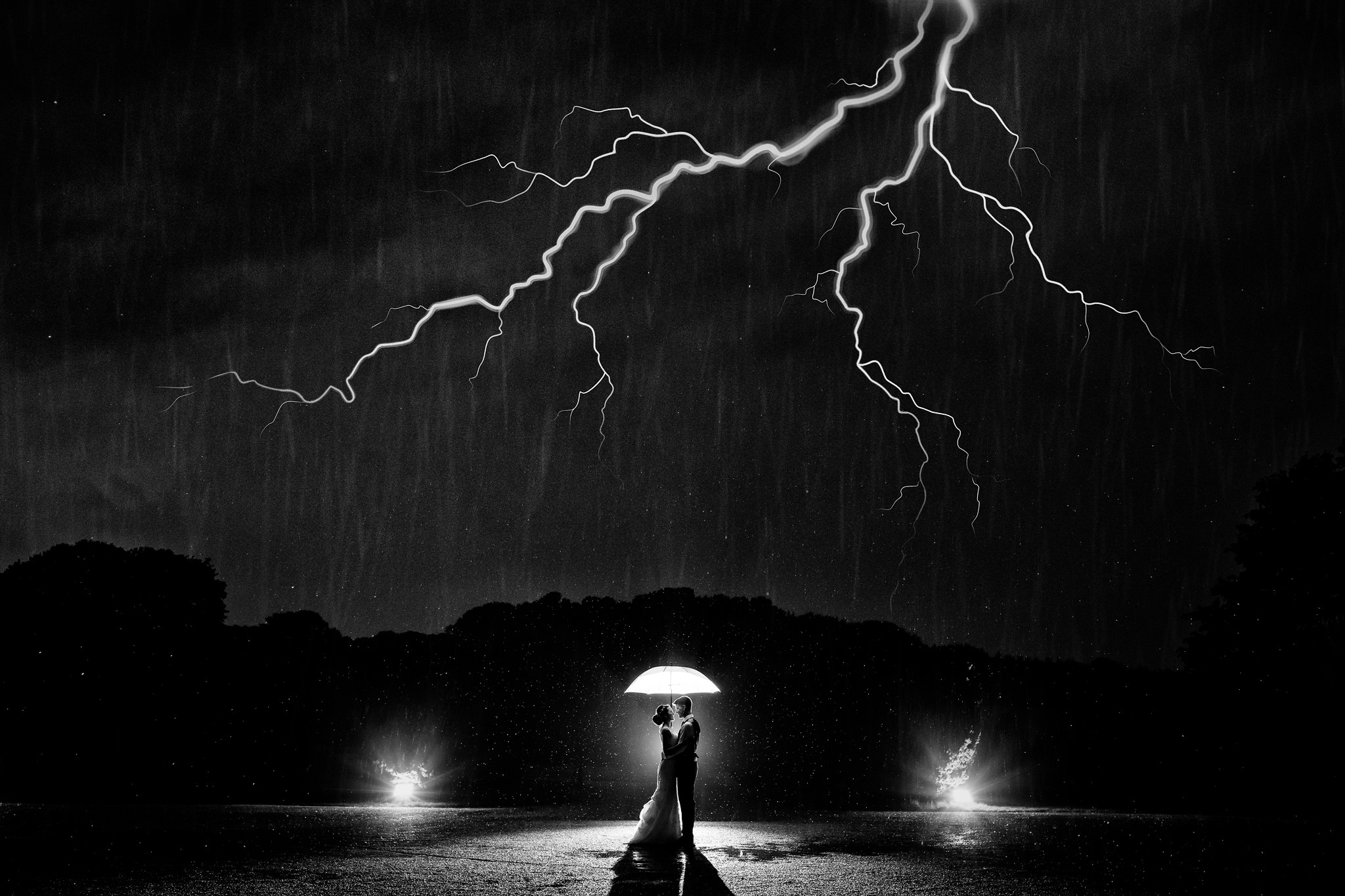 Couple under umbrella in lighting storm - photo by Rich Howman