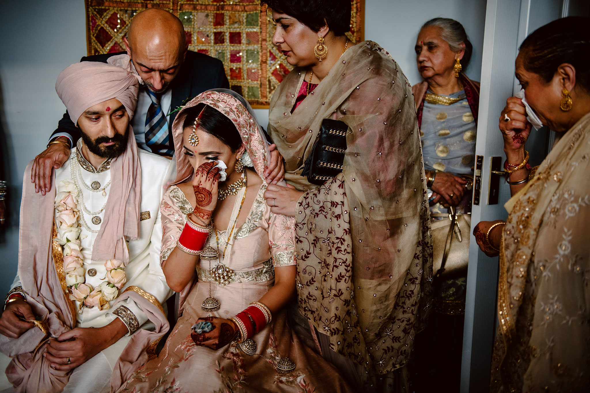 Couple with parents as bride wipes a tear - photo by Rich Howman