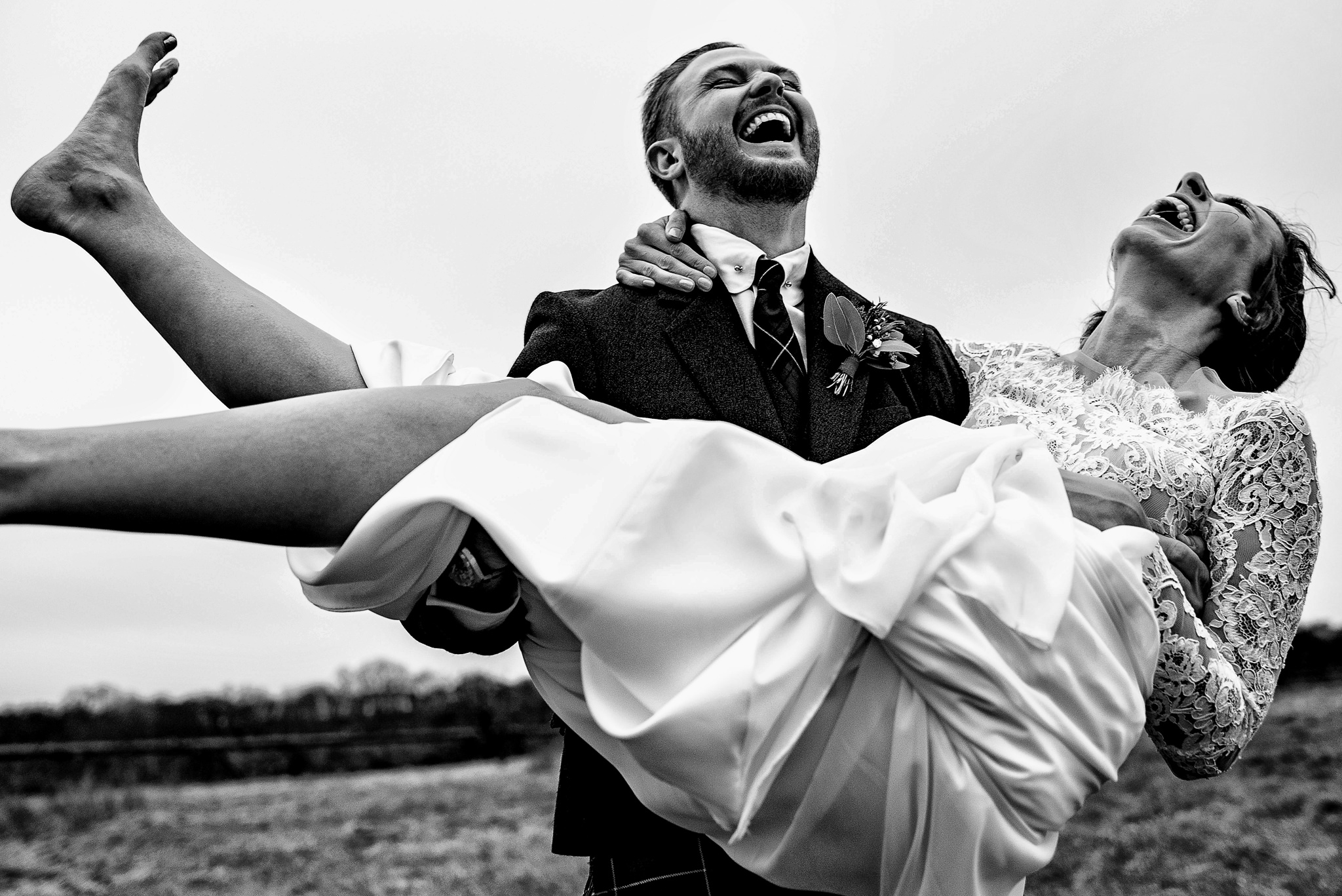 Groom holding bride while they both laugh uproariously- photo by Rich Howman