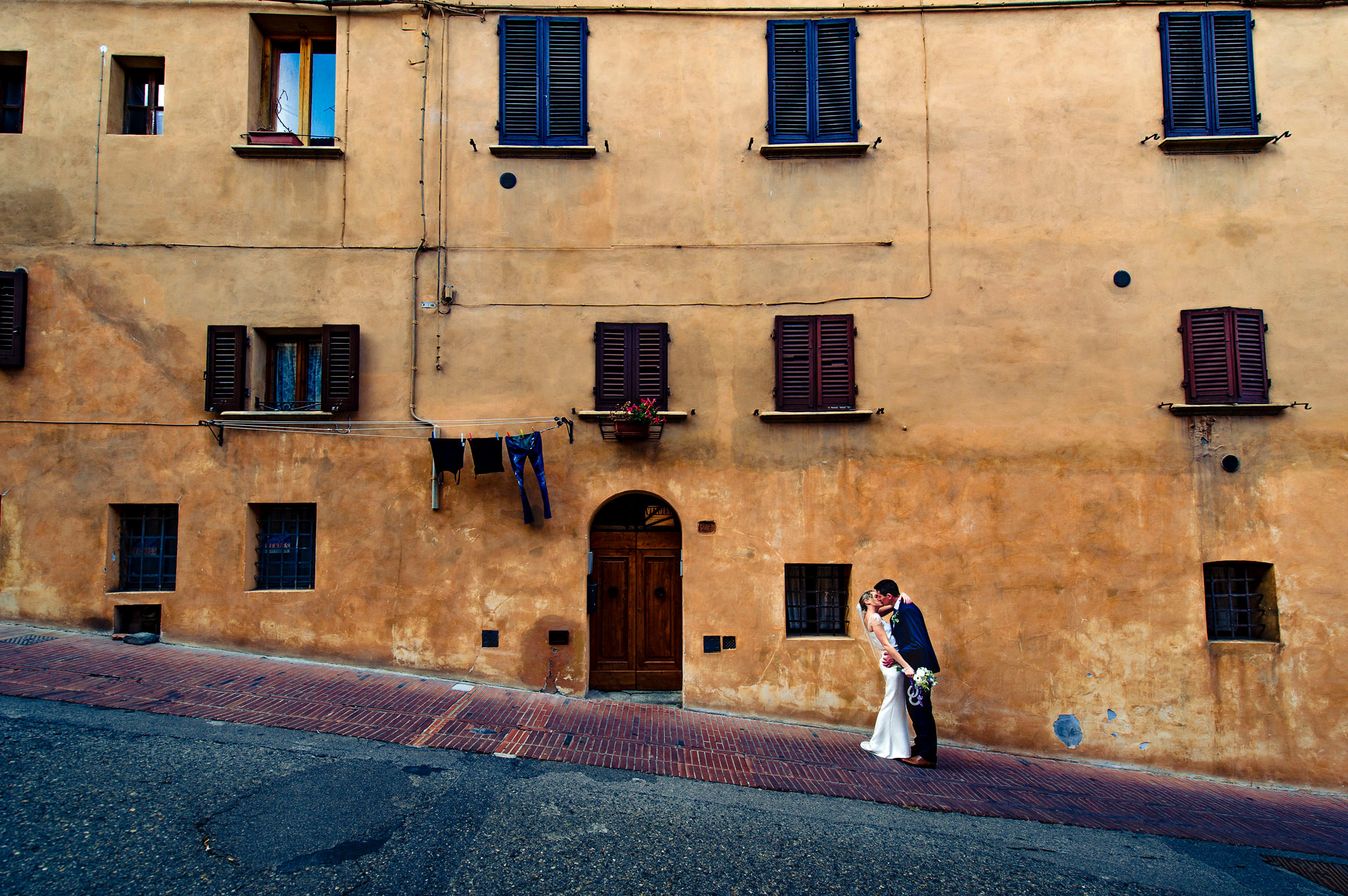 kissing-couple against rustic building - photo by Rich Howman