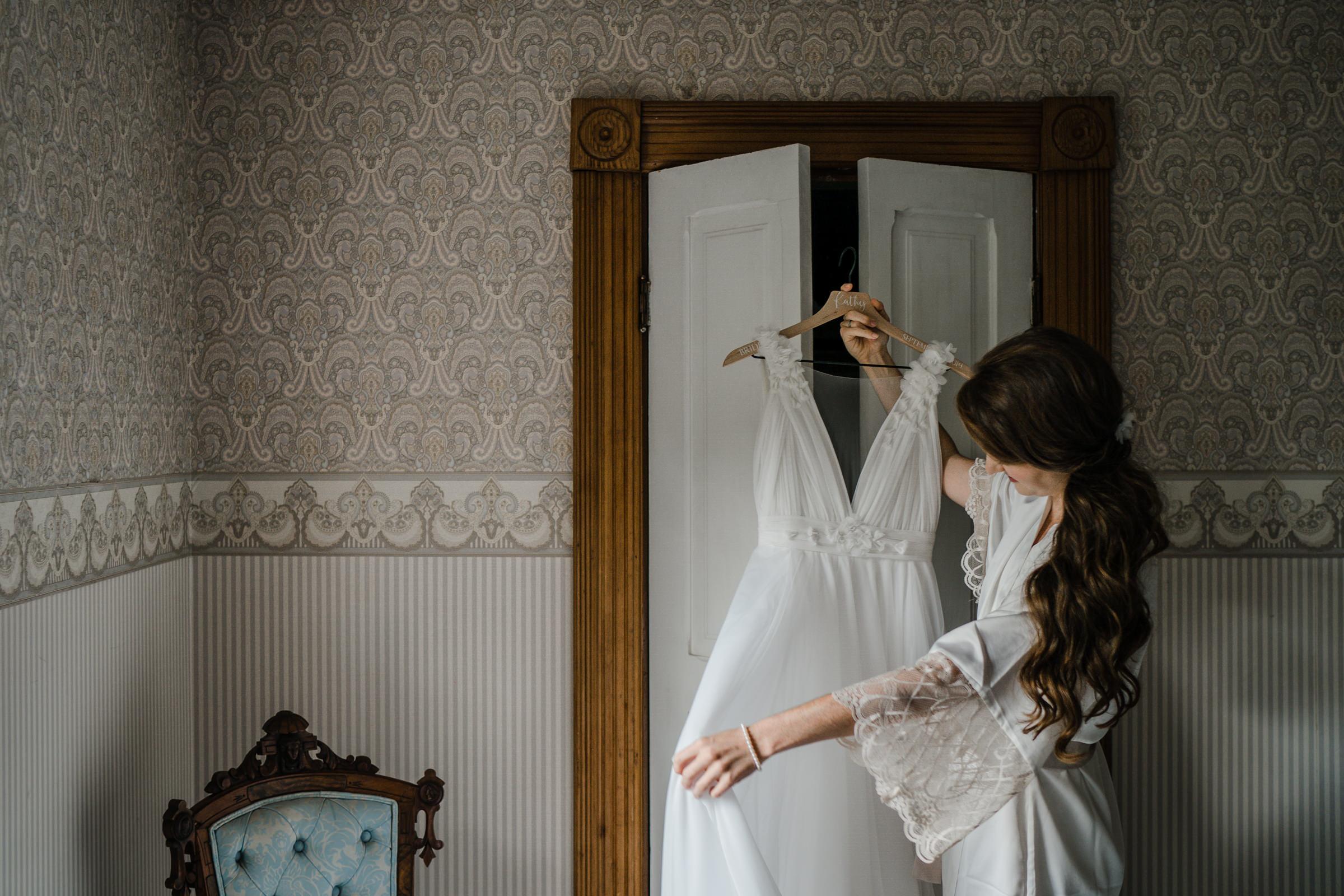 Bride admires gown on hangar - photo by Sasha Reiko Photography