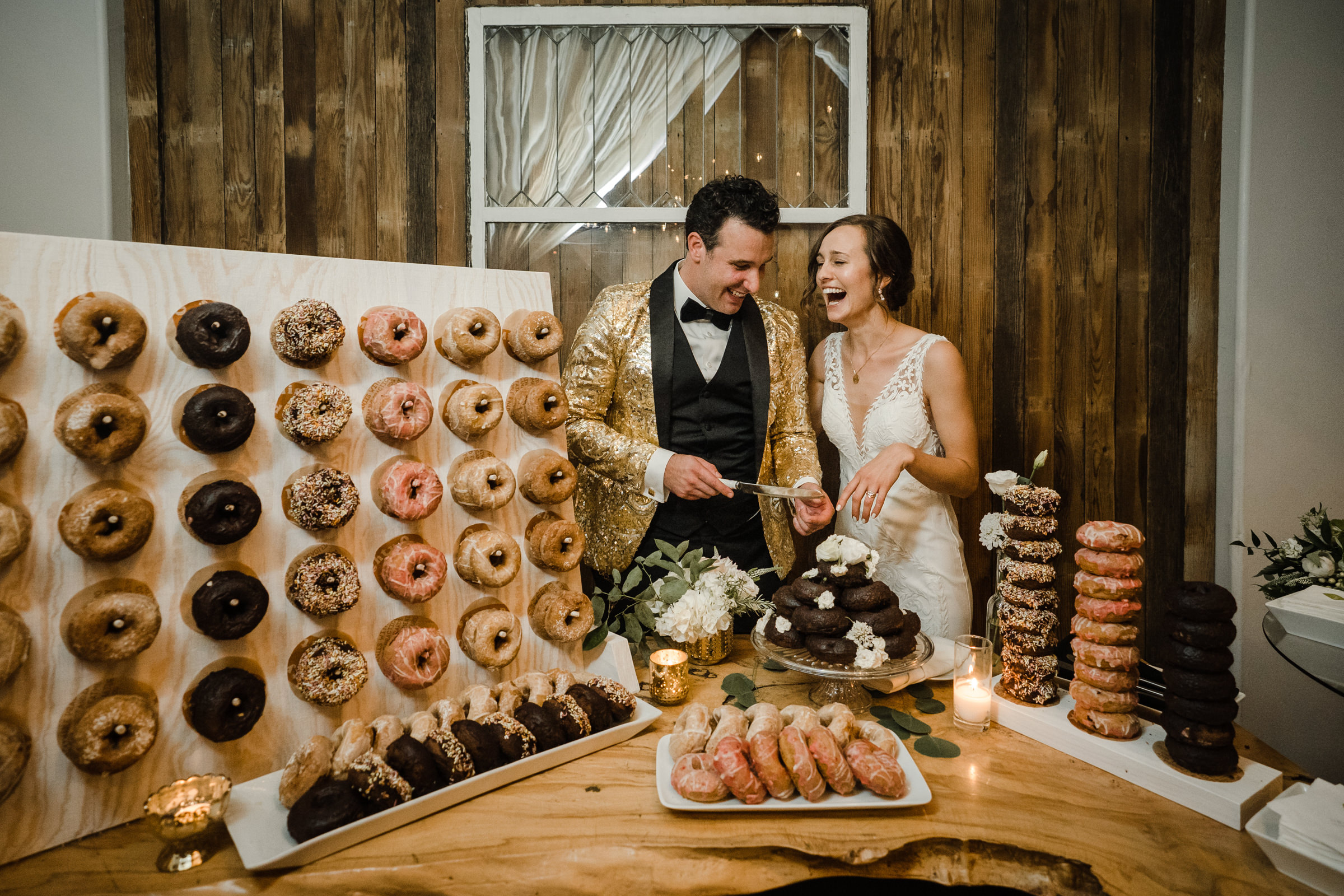 Bride and groom delighted at donut dessert table - photo by Sasha Reiko Photography