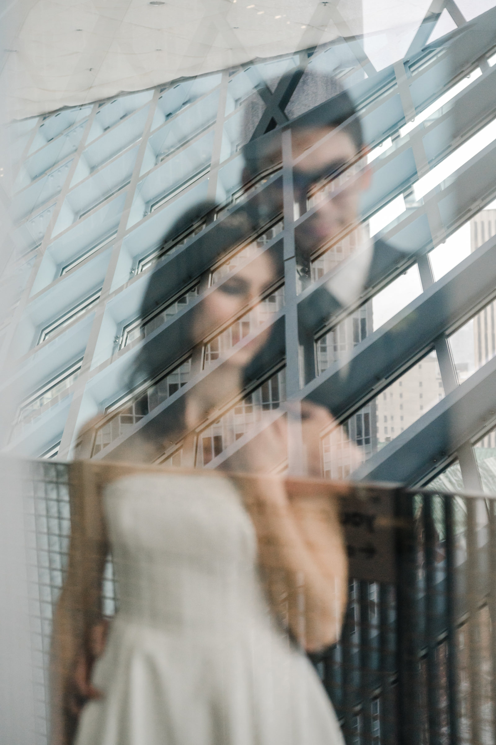 Bride and groom reflected in building - photo by Sasha Reiko Photography
