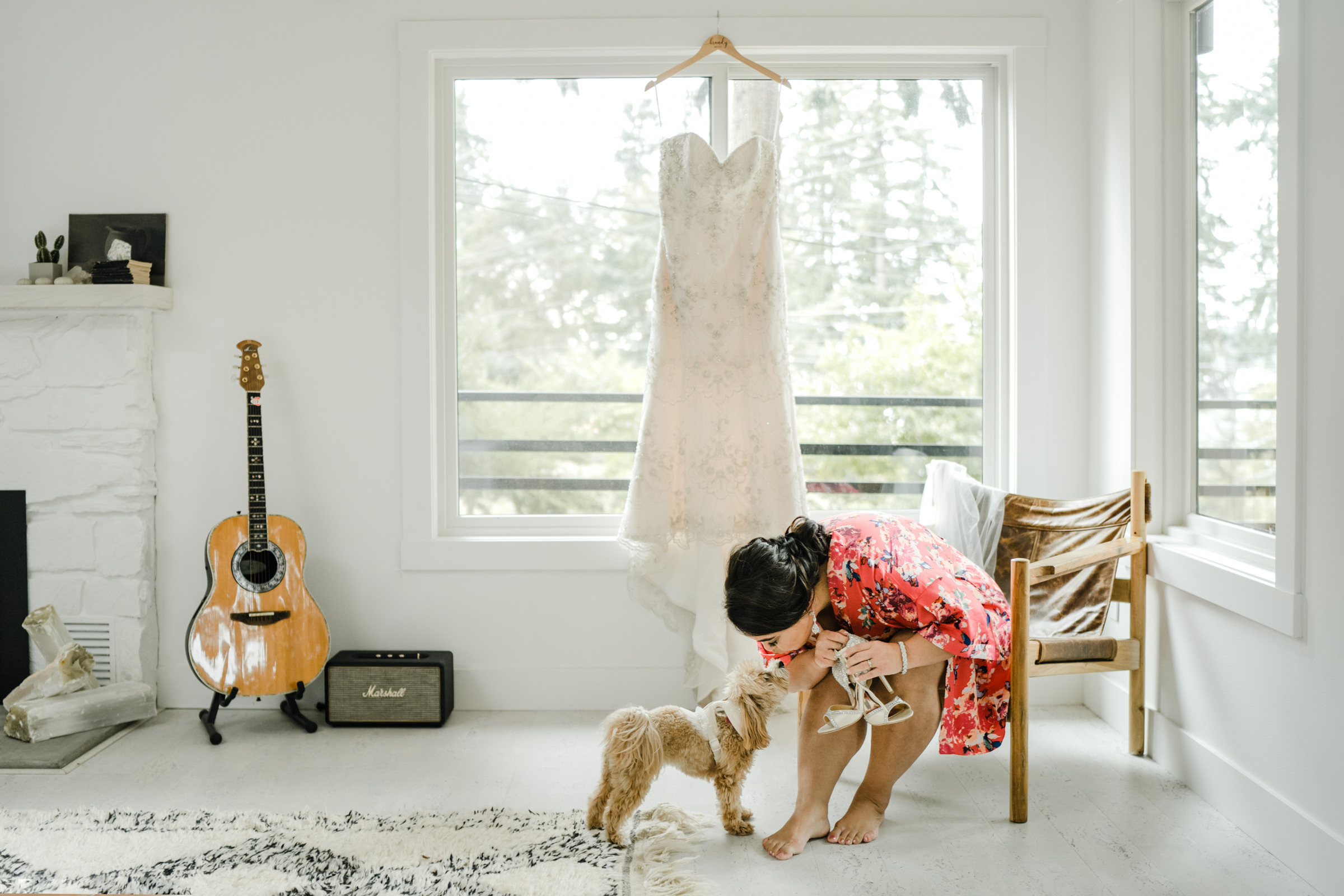 Bride in red robe kisses dog - photo by Sasha Reiko Photography