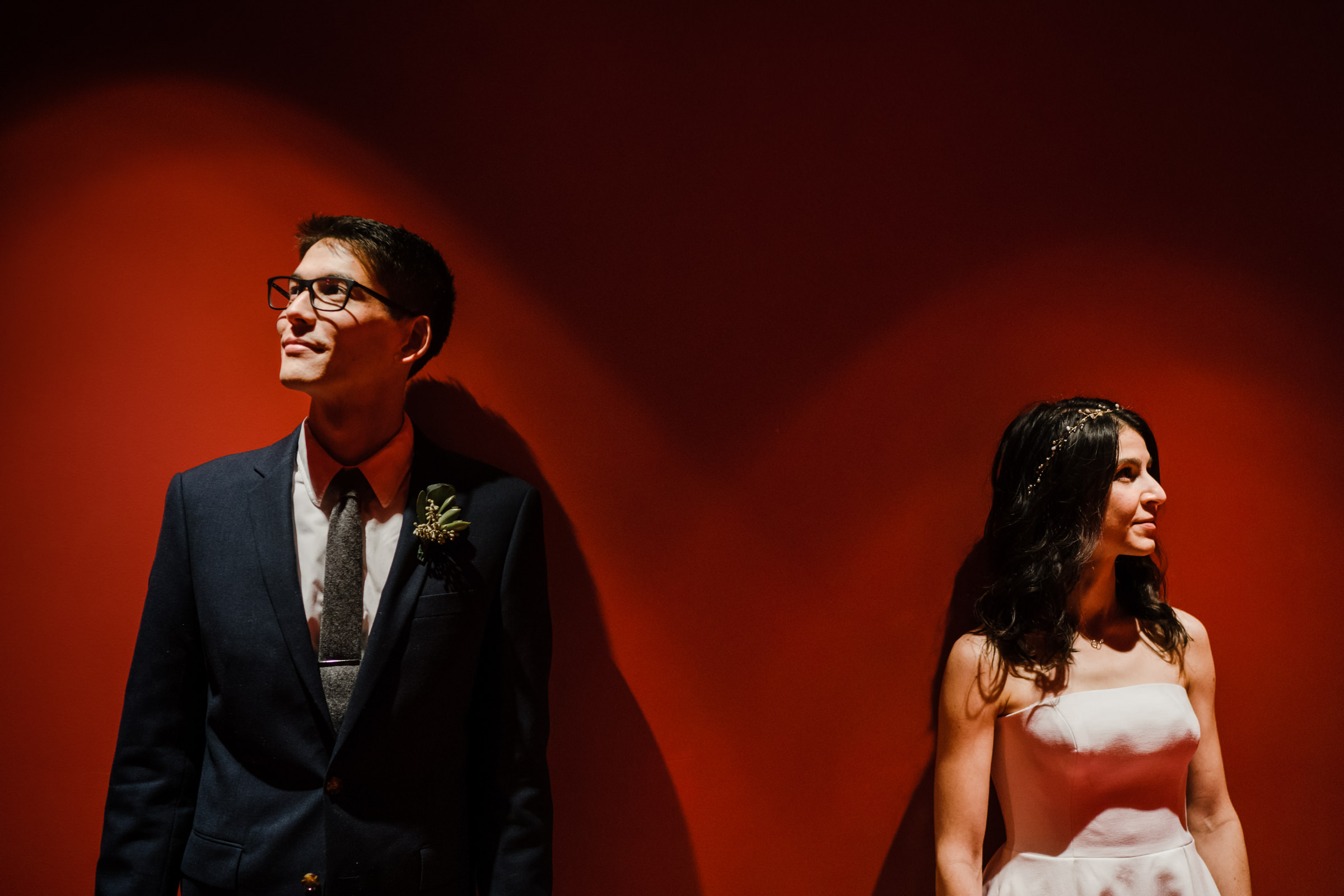 Bride and groom against red wall - photo by Sasha Reiko Photography