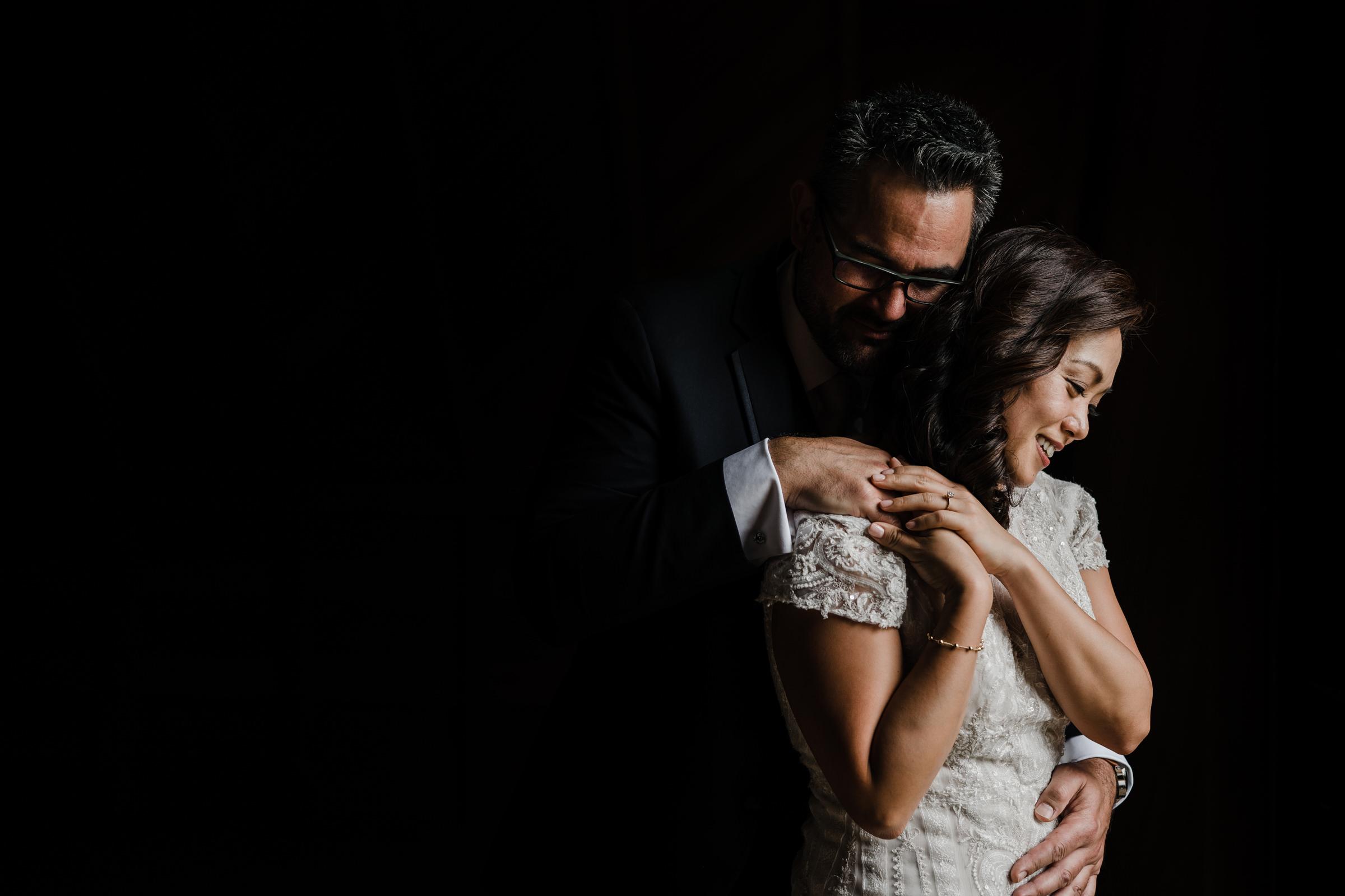 Bride and groom embrace - photo by Sasha Reiko Photography