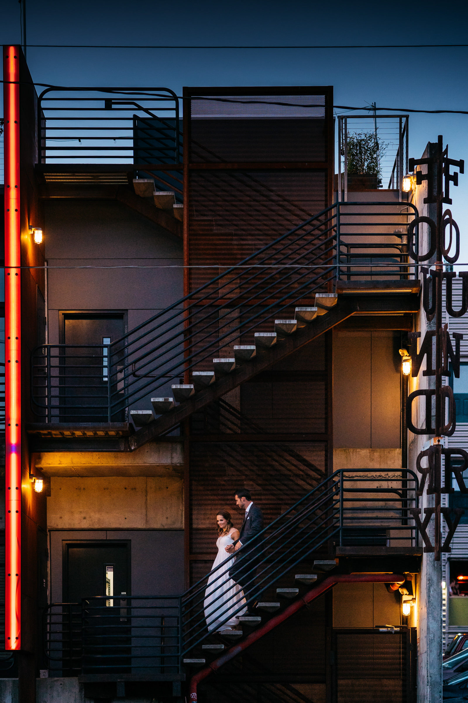 Couple descends stairs at foundry - photo by Sasha Reiko Photography