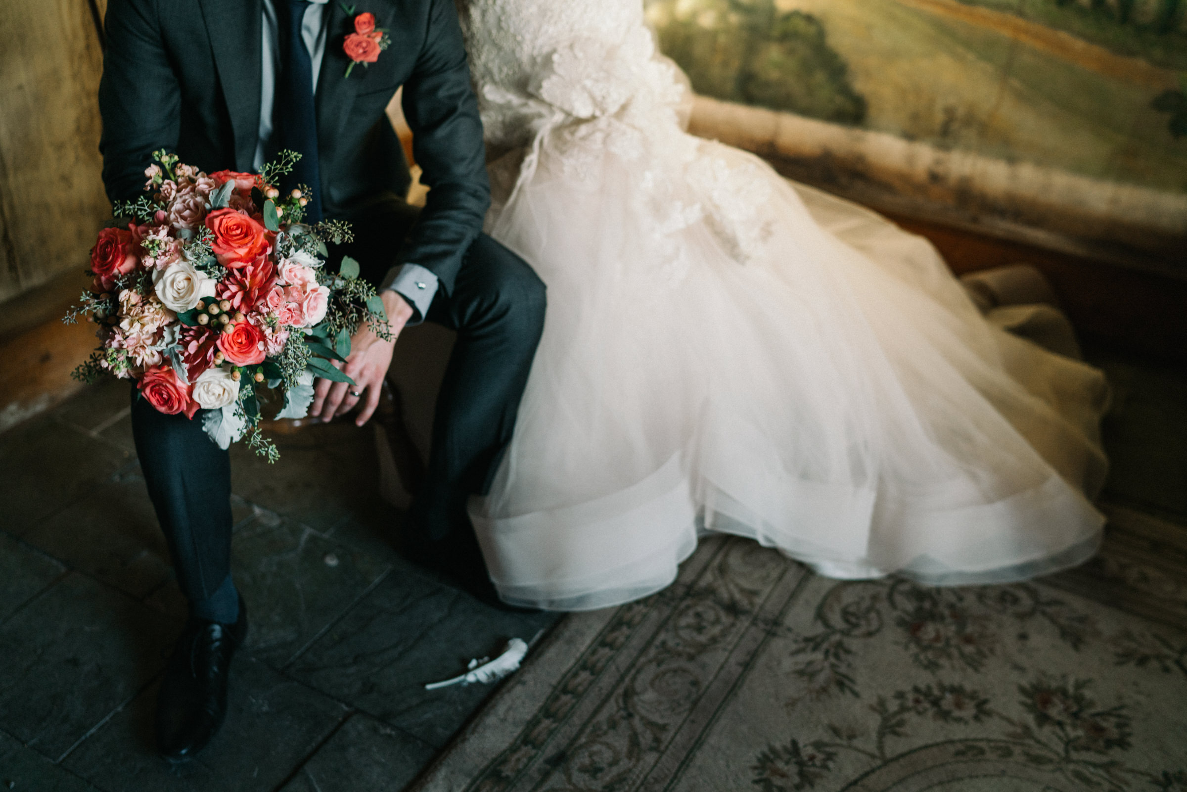 Detail of elegant bridal gown and groom with bouquet - photo by Sasha Reiko Photography