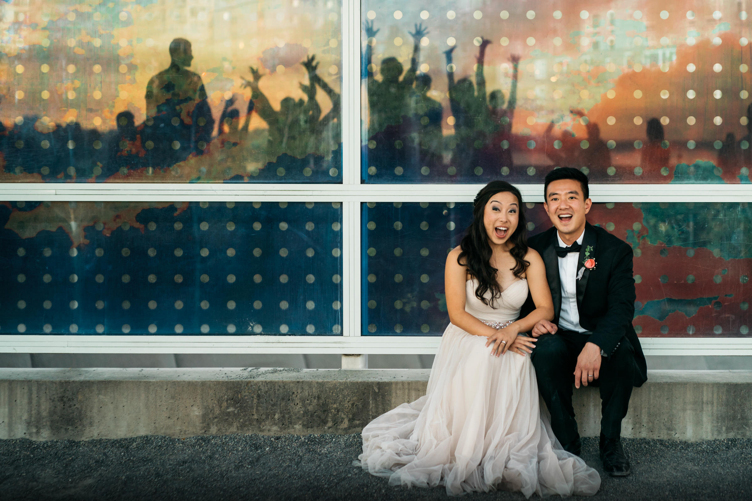 Seated couple portrait against silhouetted revelers - photo by Sasha Reiko Photography