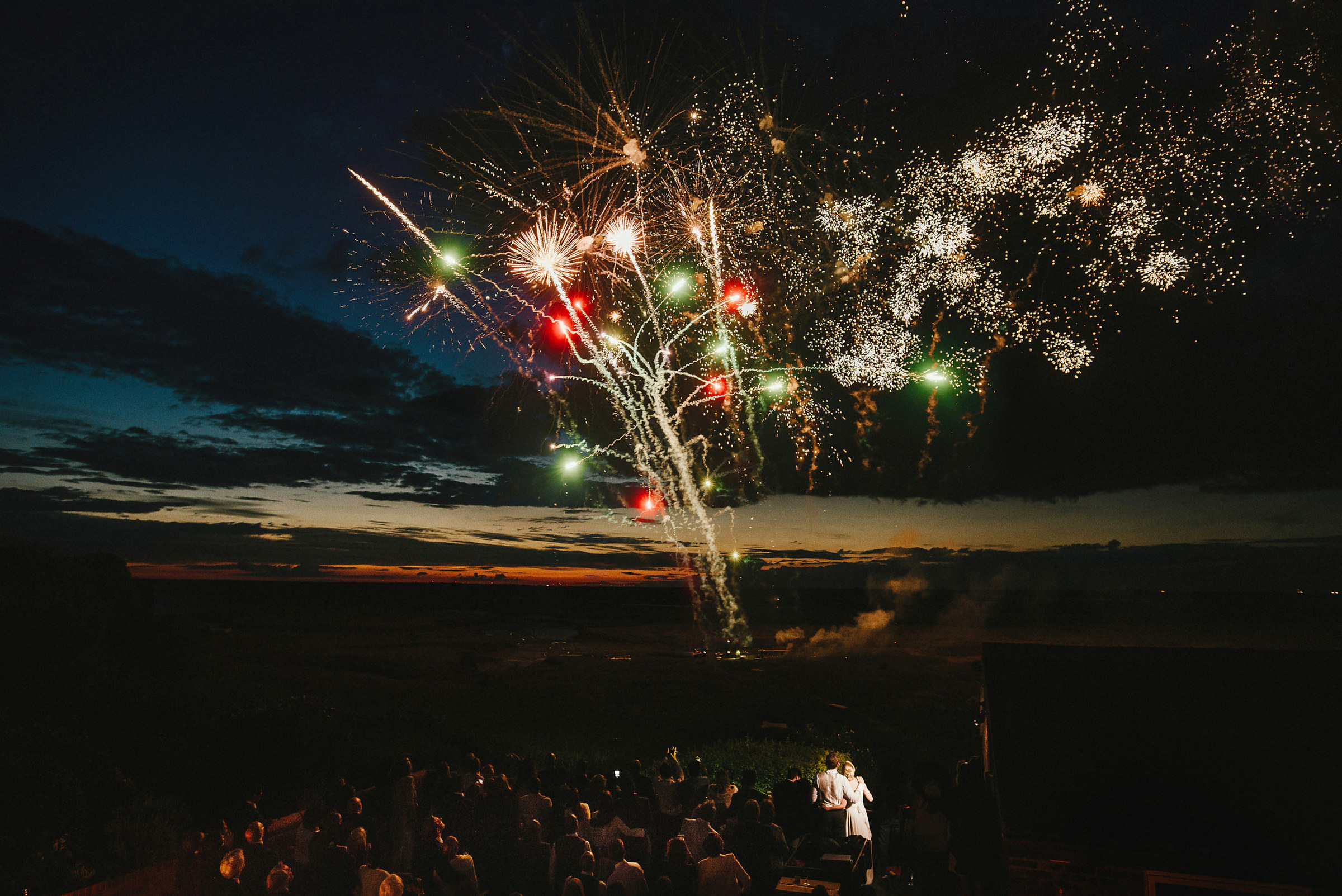 Bride and groom watch fireworks with guests photo by Andy Gaines Photography