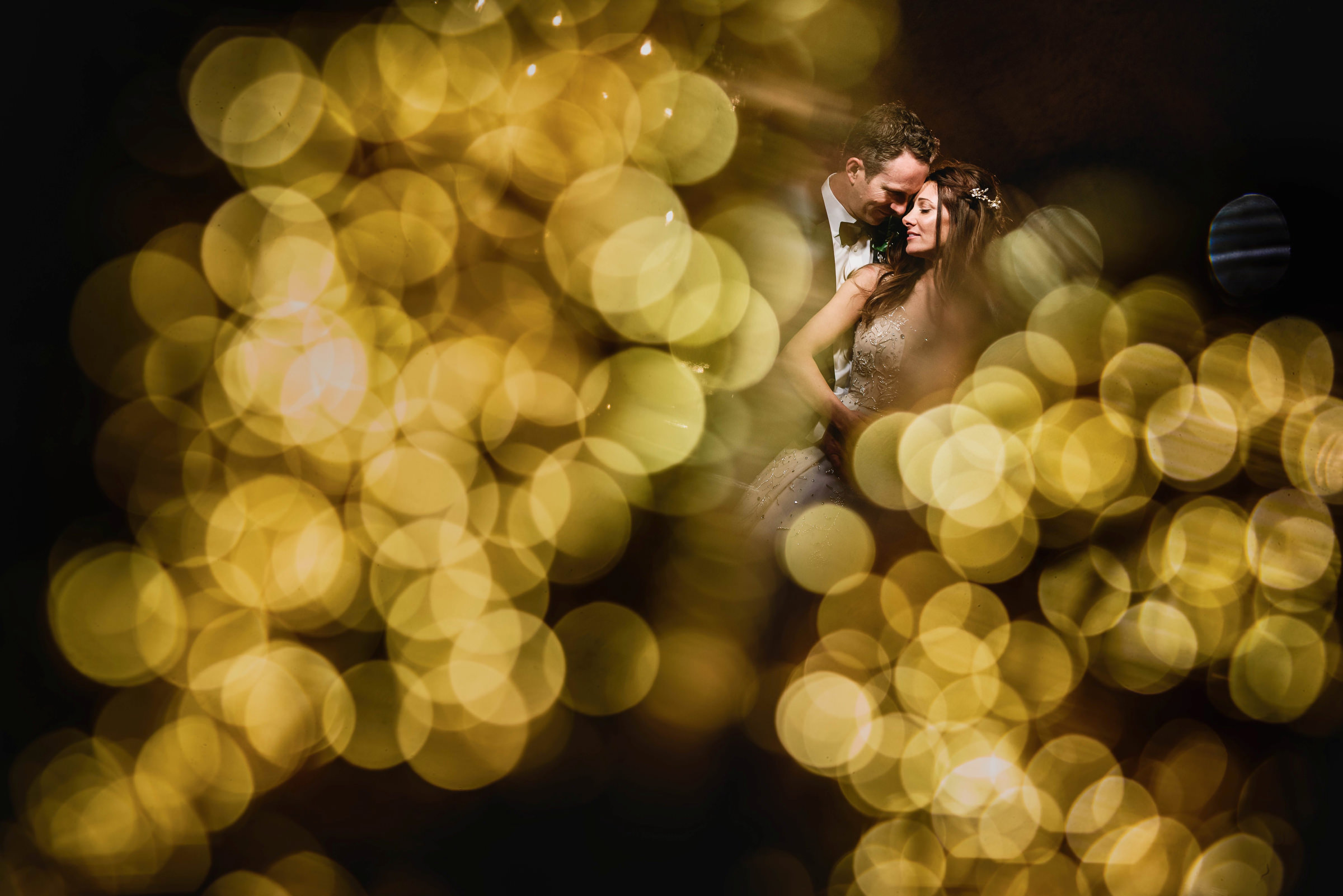 Bride and groom with bokeh lights photo by Andy Gaines Photography