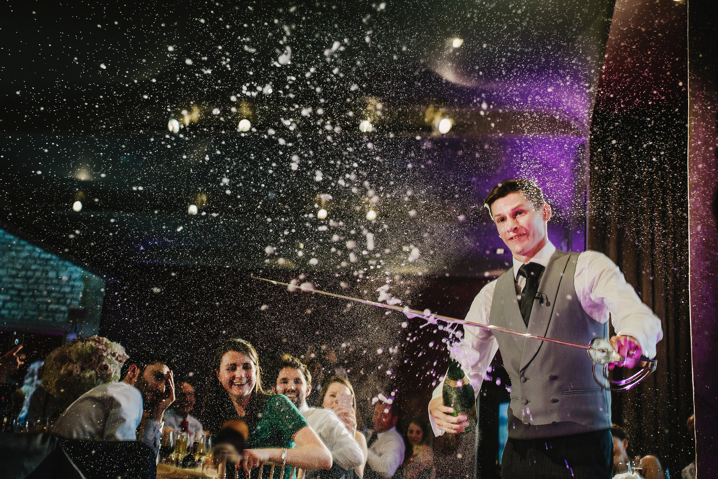 Groom cuts champagne bottle top off with sword photo by Andy Gaines Photography