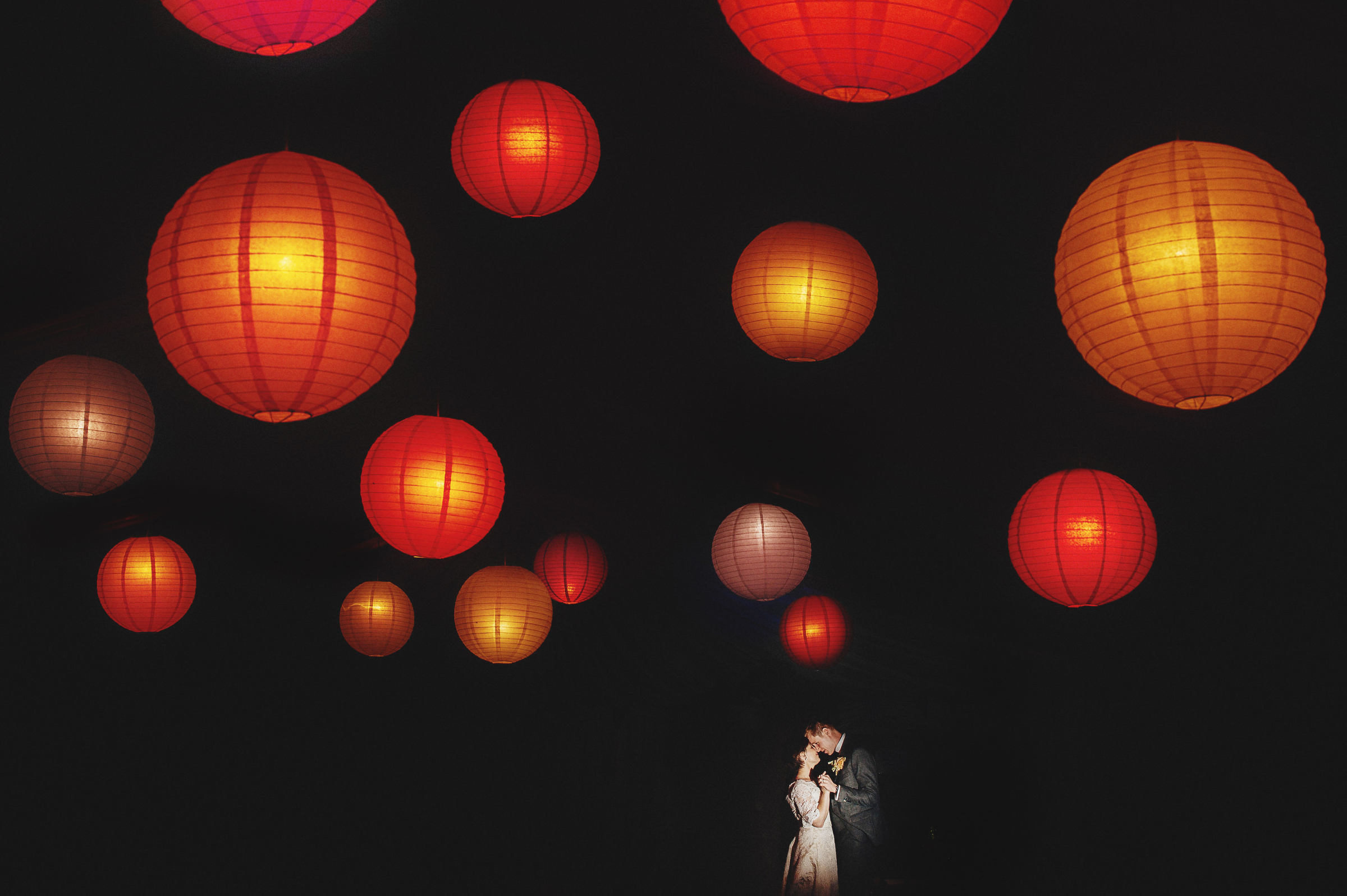 Couple dance against red paper globe lights - photo by Andy Gaines Photography