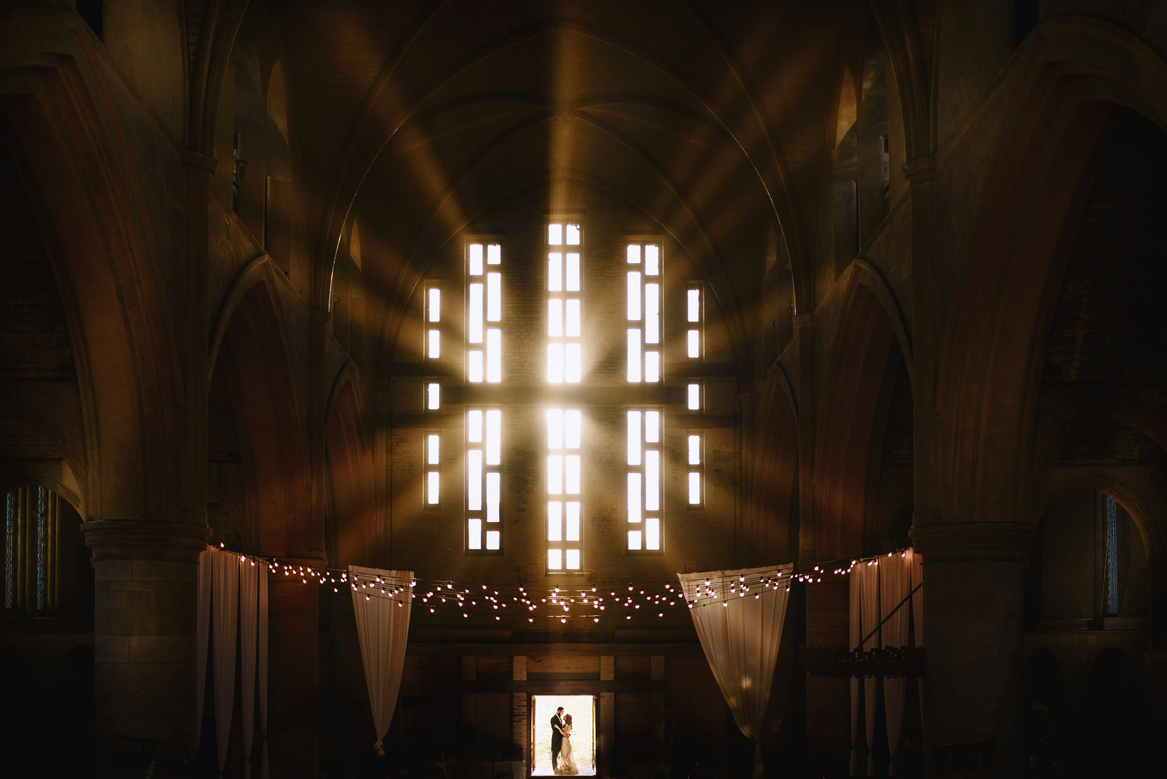 Couple portrait at church entrance with light rays coming in - photo by Andy Gaines Photography