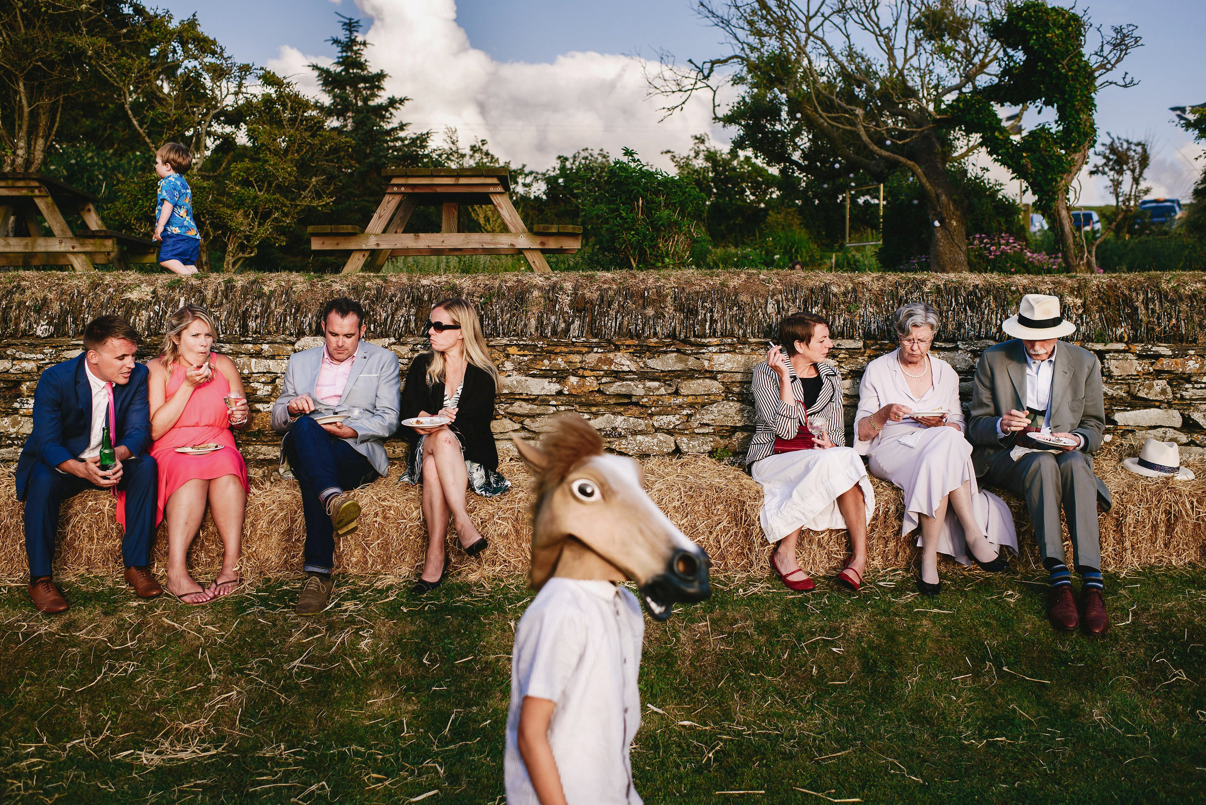 kid in horse mask and guests at outdoor reception - photo by Andy Gaines Photography